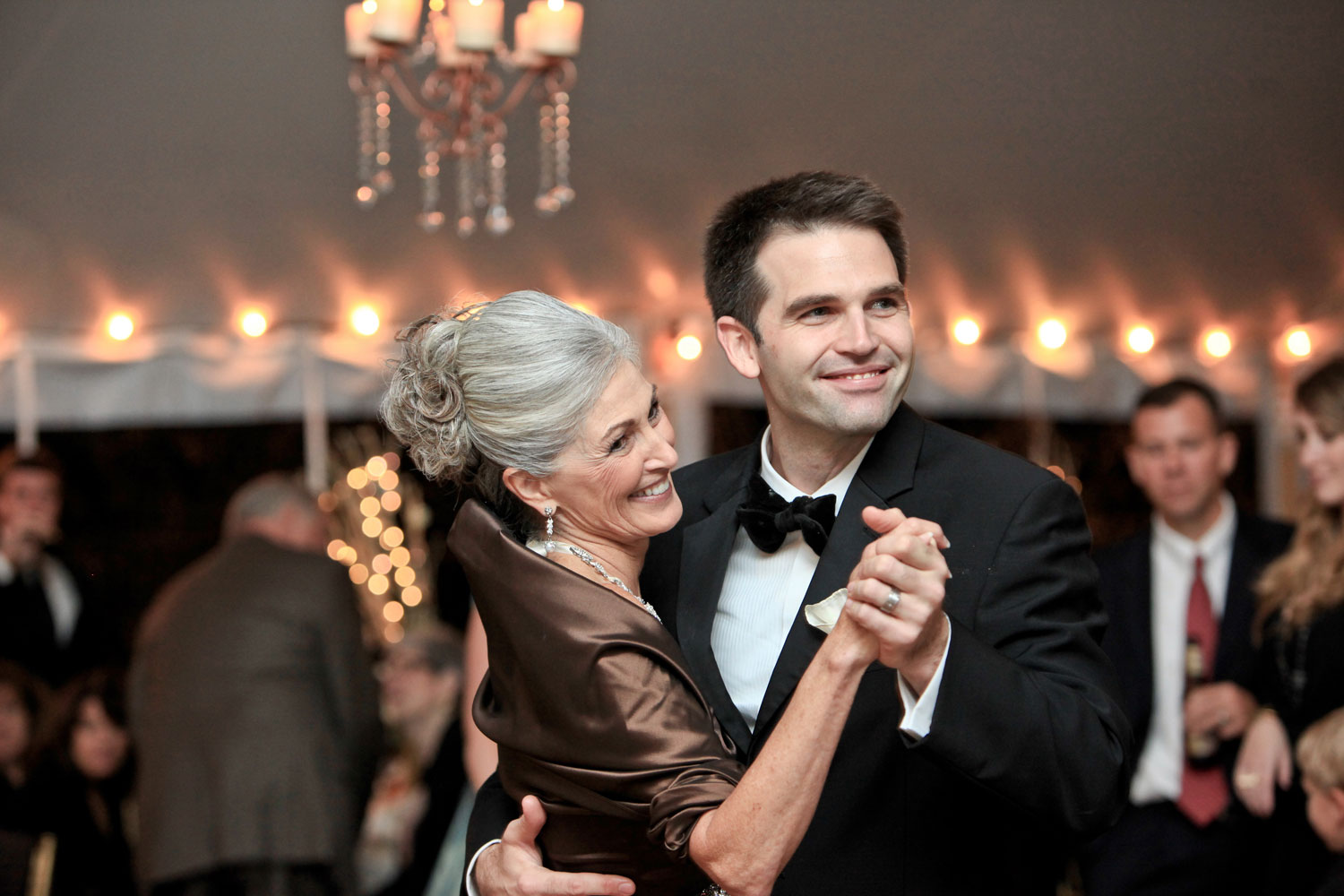 Cute mother of bride in evening gown dancing with son during mother son dance