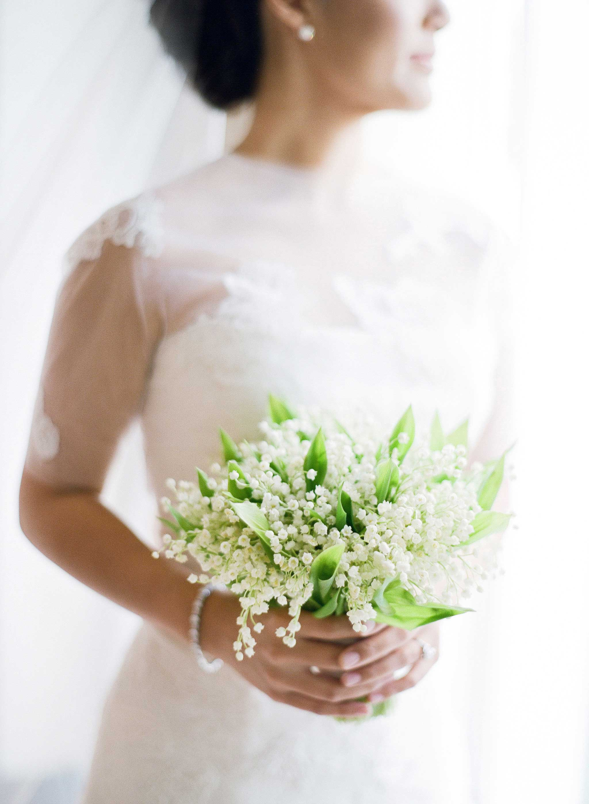 Bride holding small lily of the valley bouquet royal wedding inspiration