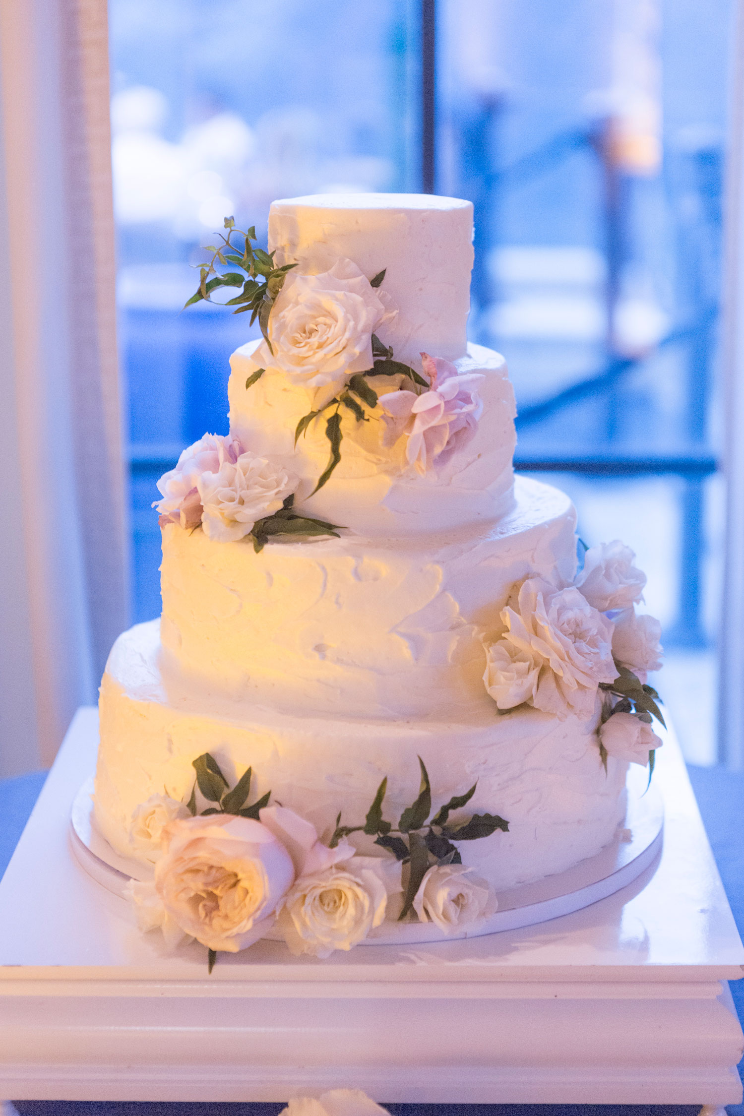 Simple white wedding cake buttercream frosting with fresh flower decorations royal wedding inspiration