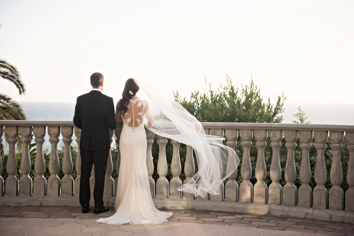 Bride in Anne Barge wedding dress with blowing veil looking at ocean from venue terrace