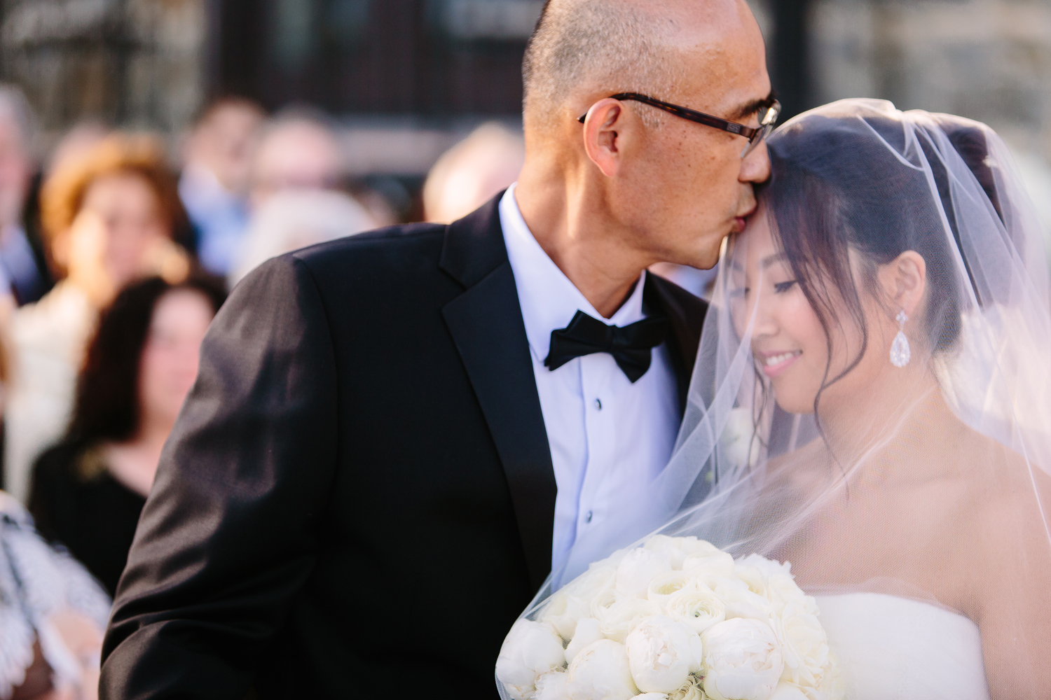 Father of bride kissing bride on head before wedding ceremony