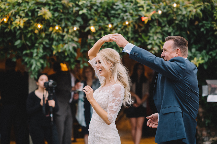 Bride in Oleg Cassini wedding dress dancing with father of bride at wedding outdoor reception