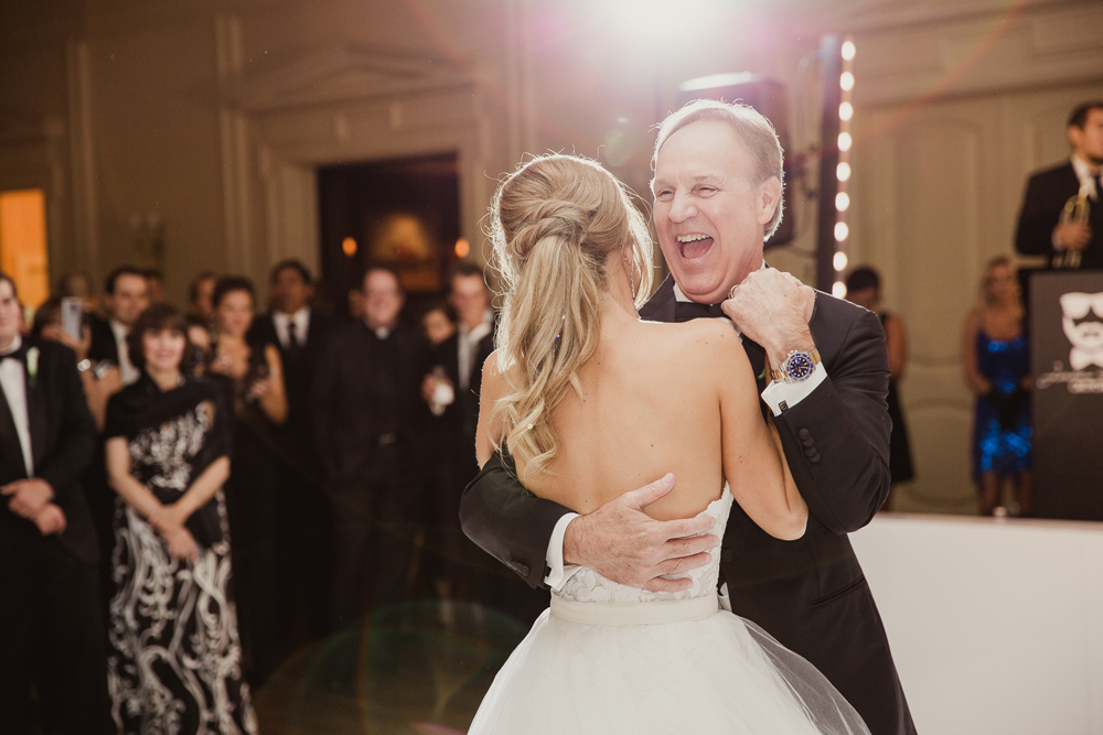 Father of bride smiling and laughing during father daughter dance at wedding