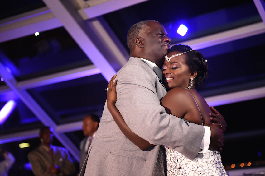 Bride with tiara hugging father of bride during father daughter dance