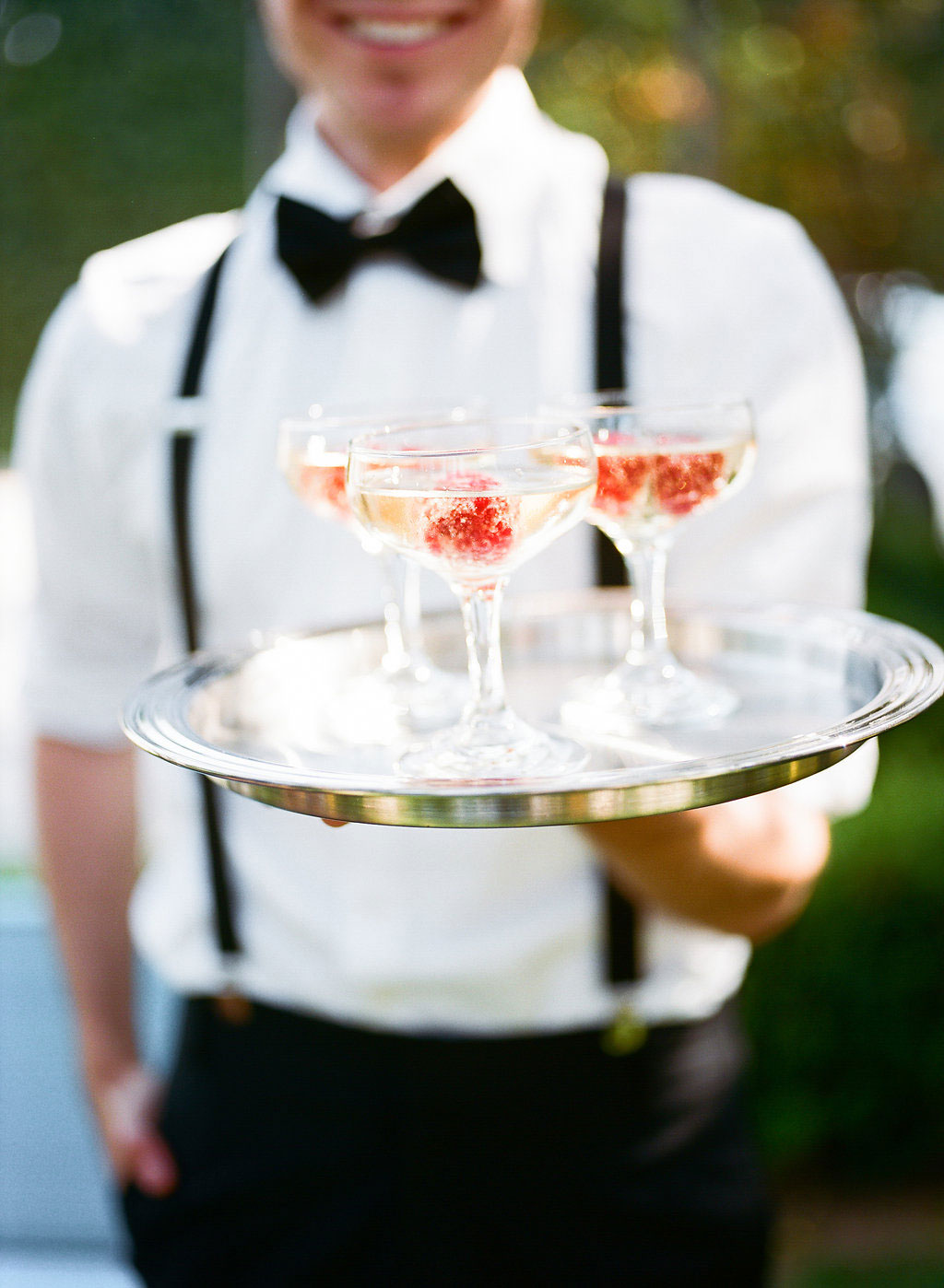 Server holding cocktail tray in coupe glass raspberry champagne