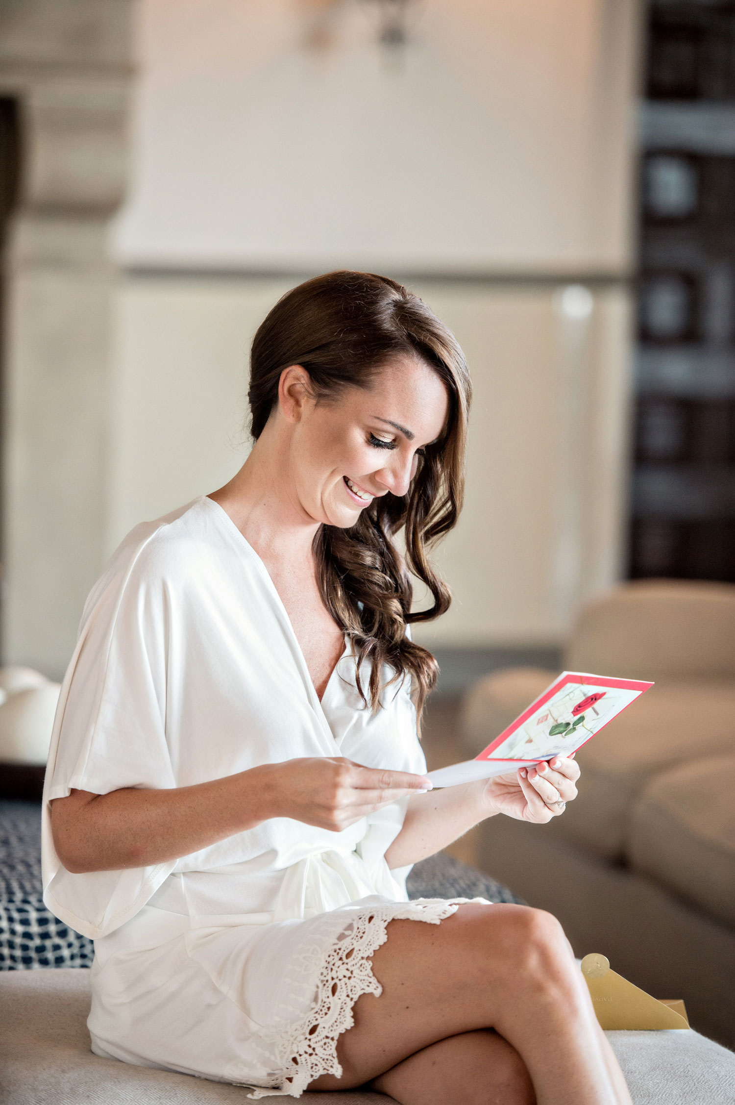 Bride reading card from groom or family member in white robe bride