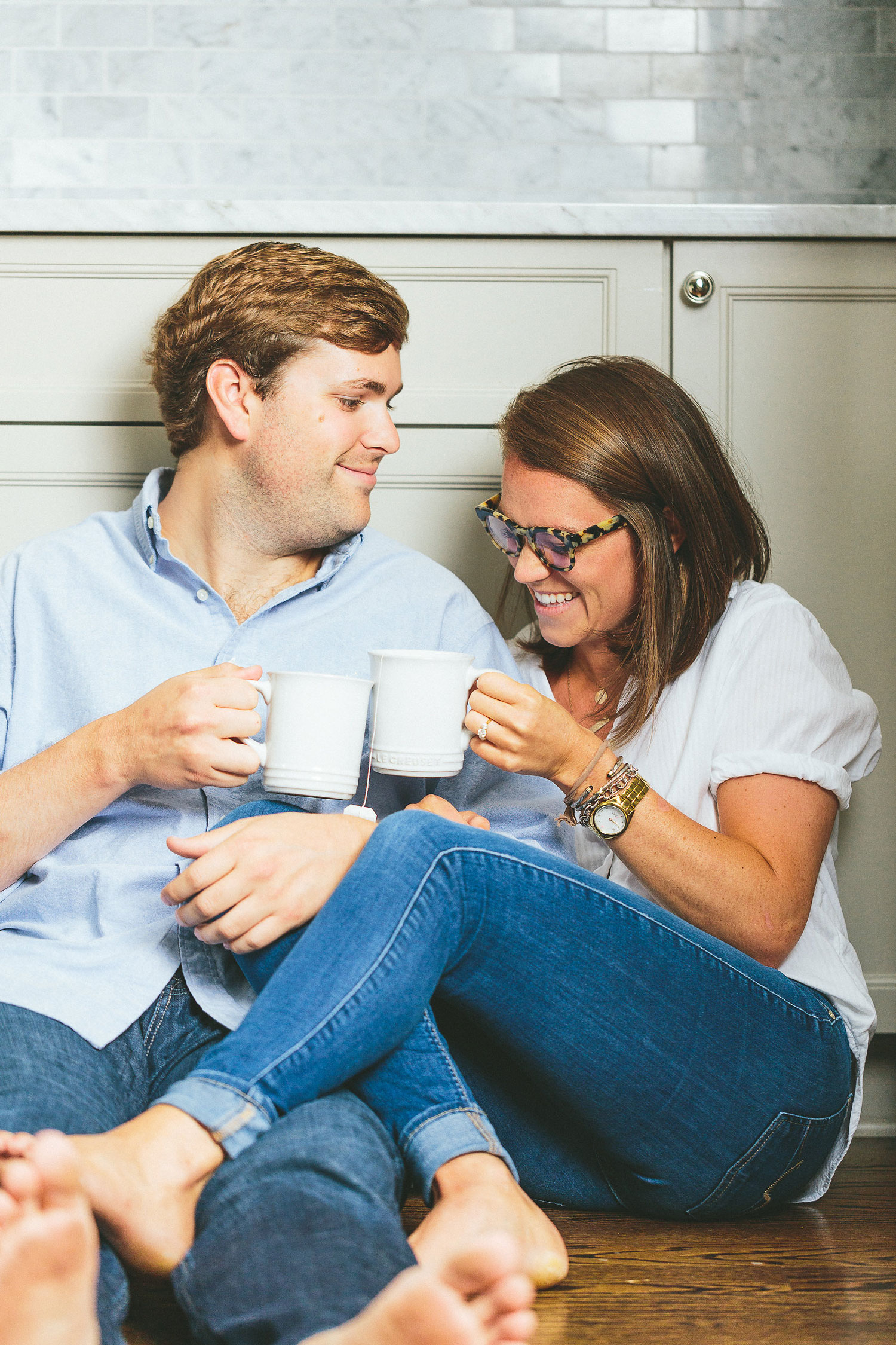 At home engagement session photo shoot in the kitchen laughing with coffee and tea on wood floor