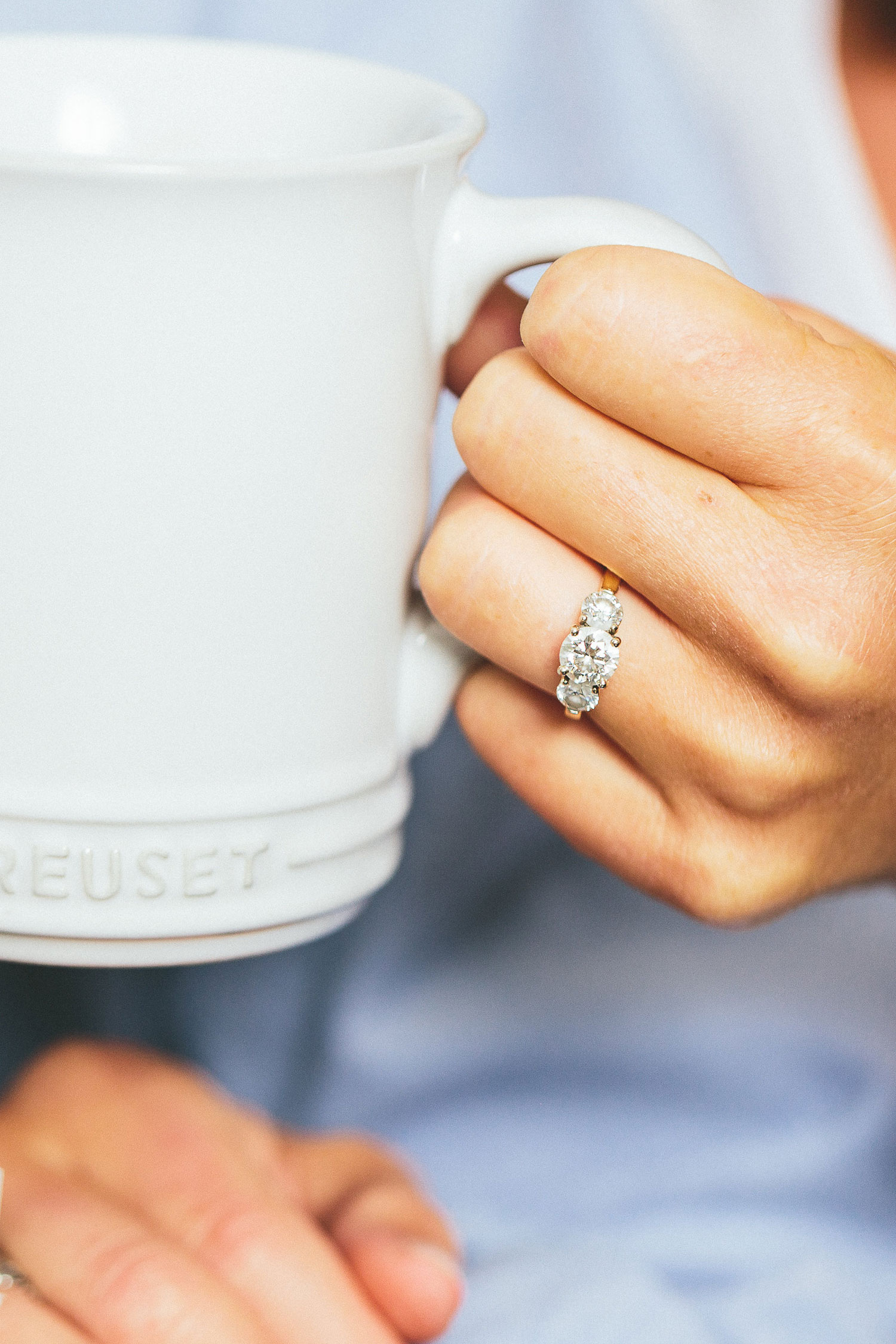 At home engagement session photo shoot in the kitchen close up of engagement ring with coffee tea cup