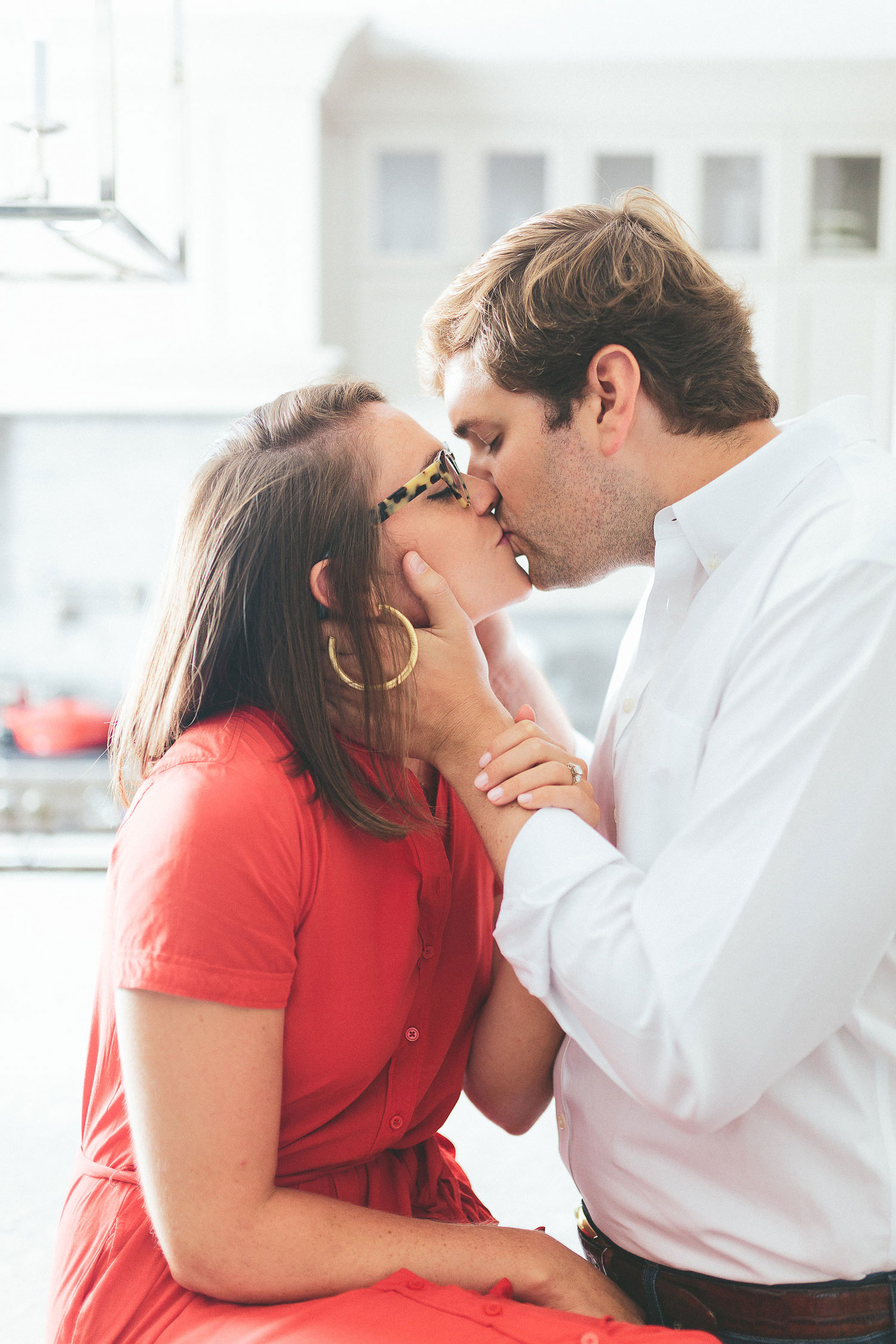 At home engagement session photo shoot in the kitchen bride in red dress kissing groom in kitchen