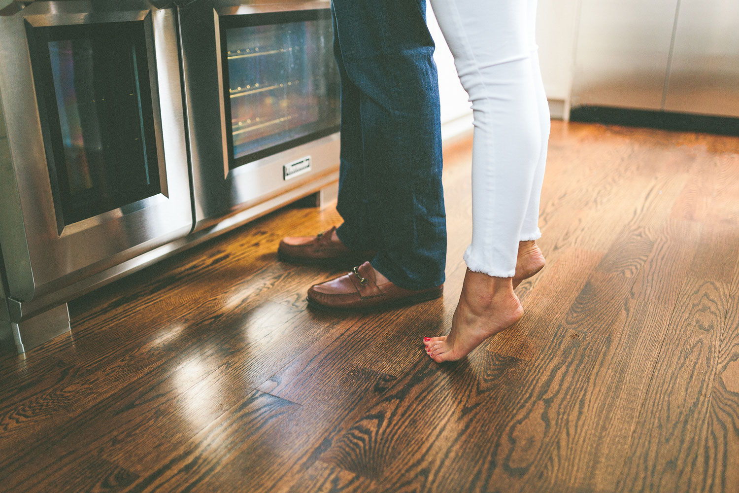 At home engagement session photo shoot in the kitchen bride on tip toes white jeans