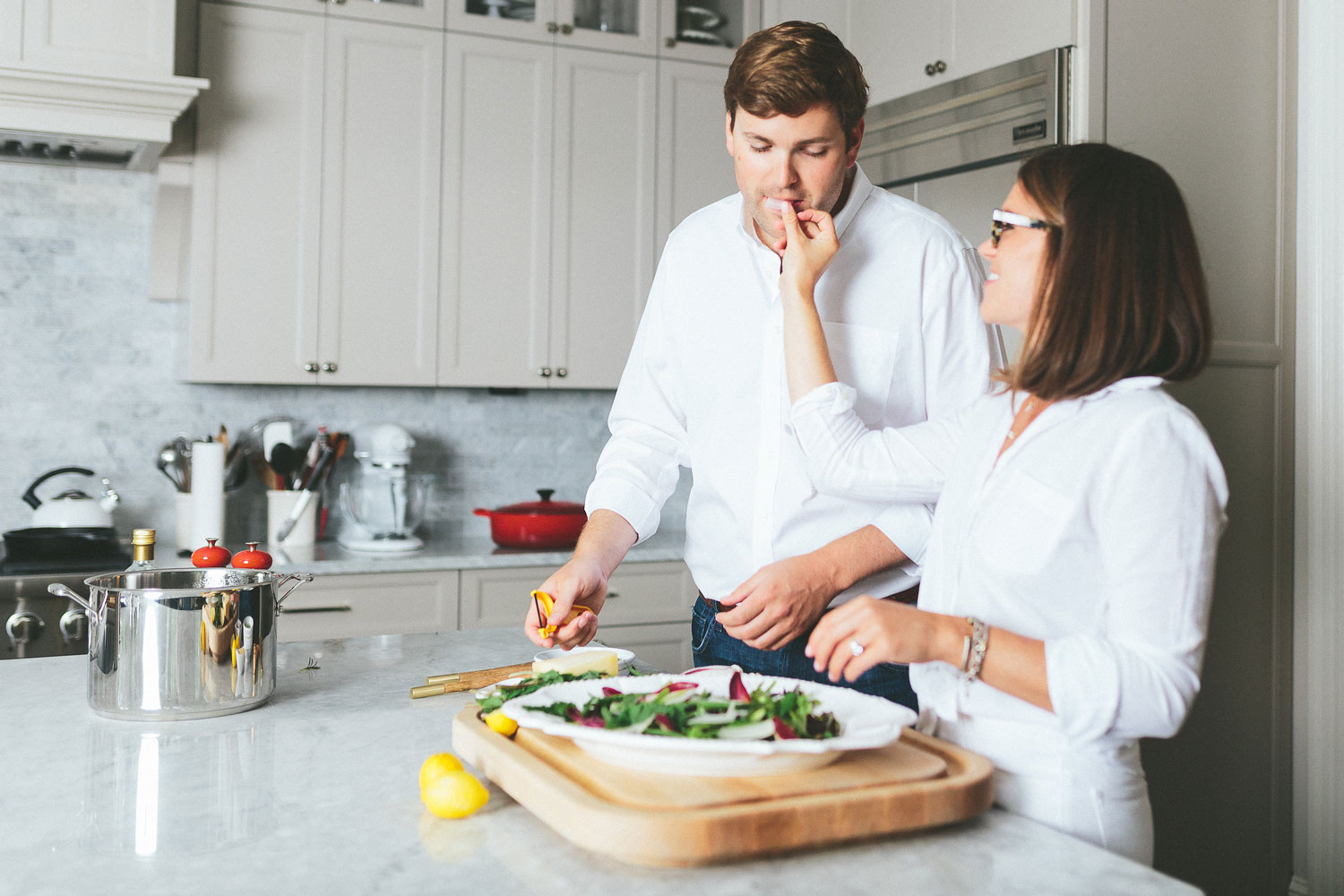At home engagement session photo shoot in the kitchen feeding groom salad e-session ideas