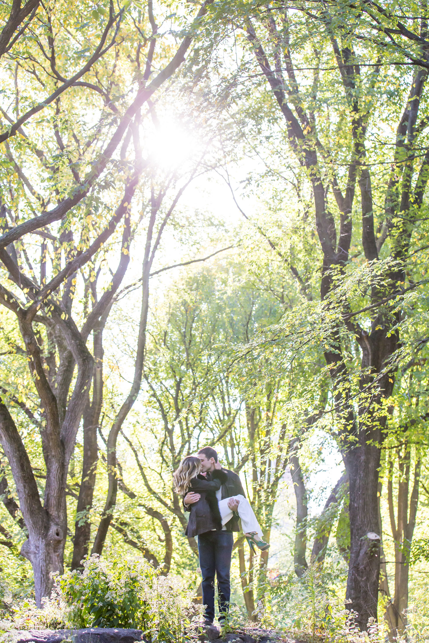 engagement shoot ideas new york city central park groom holding bride with trees in background