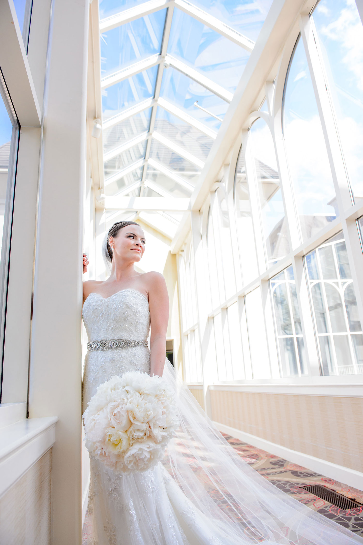 Bride in strapless wedding dress white bouquet looking out window bridal tips