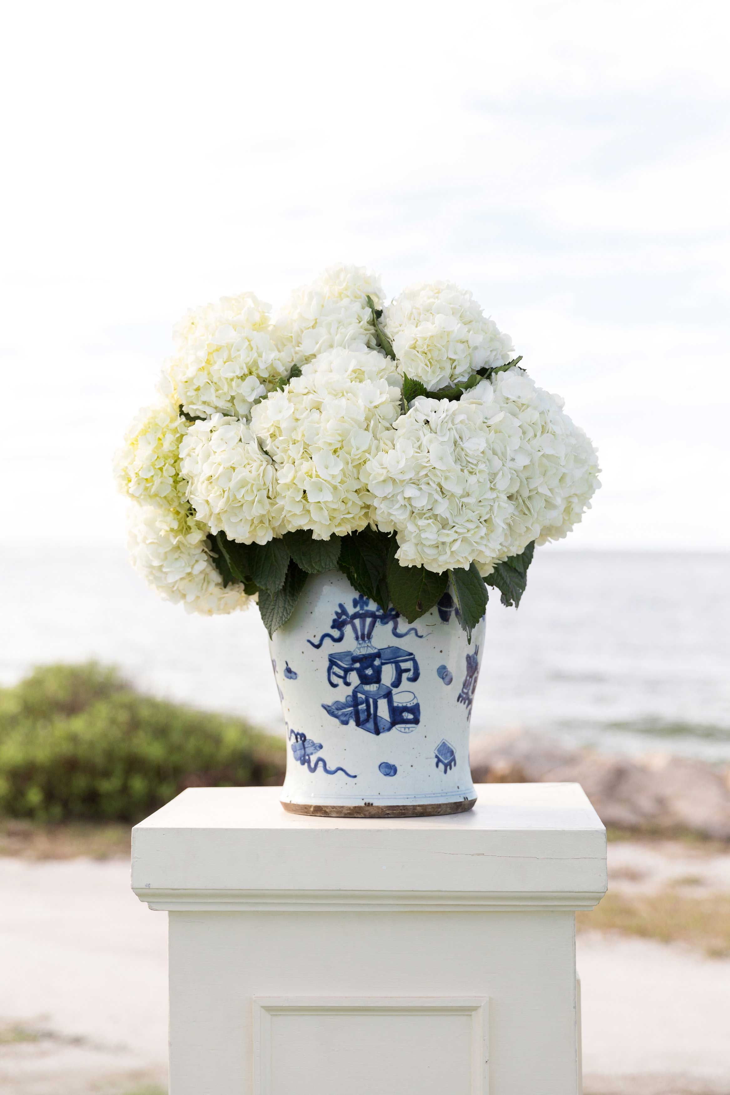Wedding ceremony by water blue and white vase ginger jar with white flowers