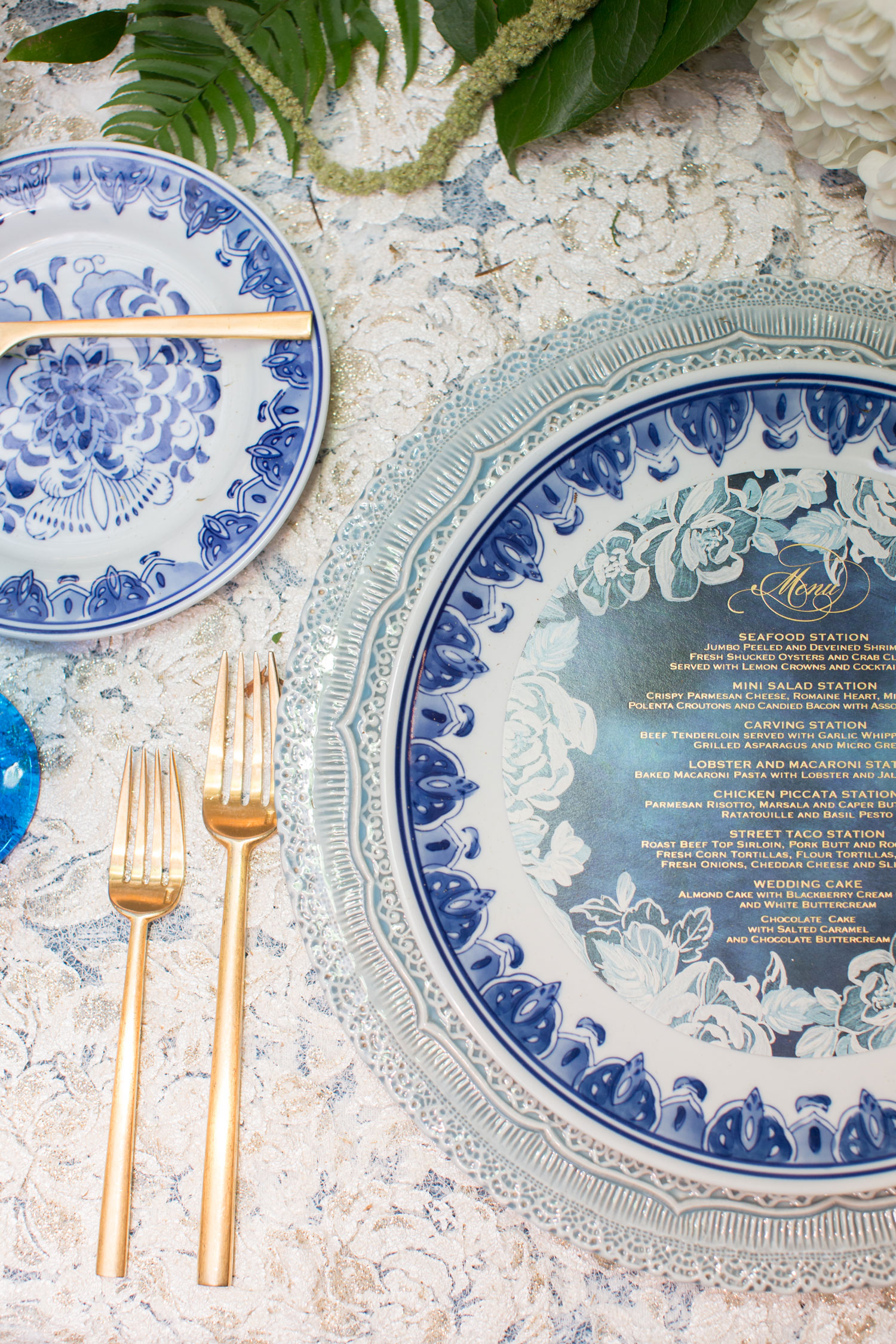 Wedding reception table blue and white china plate with blue menu card gold flatware