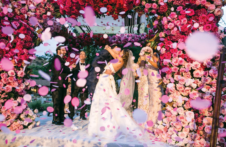 Bride and groom kiss under pink flower chuppah outdoor wedding samuel lippke gellery events Inside Weddings fall 2018 issue