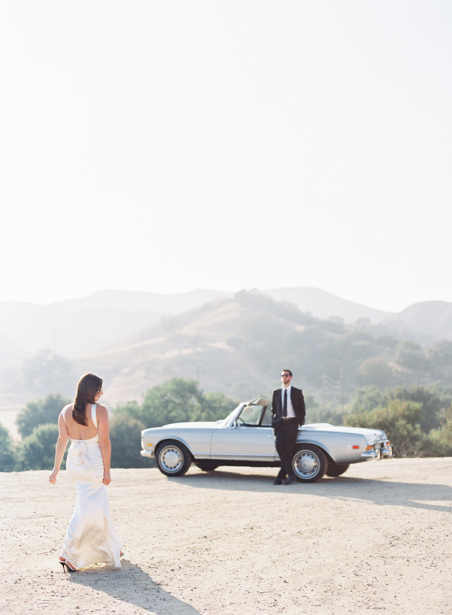 Engagement shoot photo ideas malibu classic car vintage mustang convertible bride walking toward groom