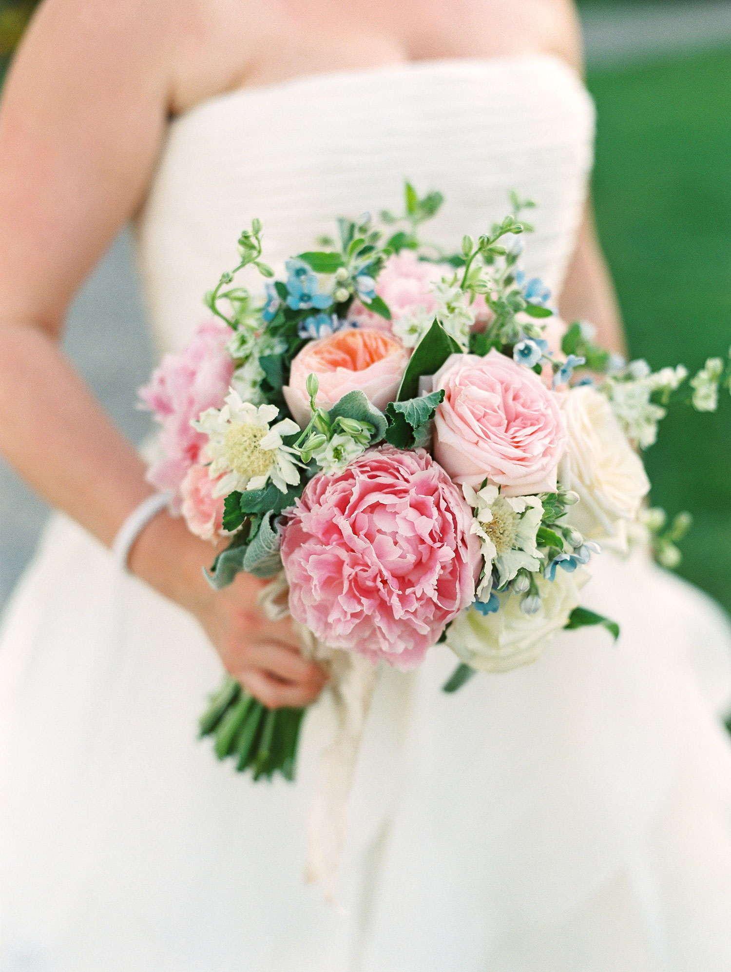 Bride holding bouquet with pink peony rose garden rose flowers