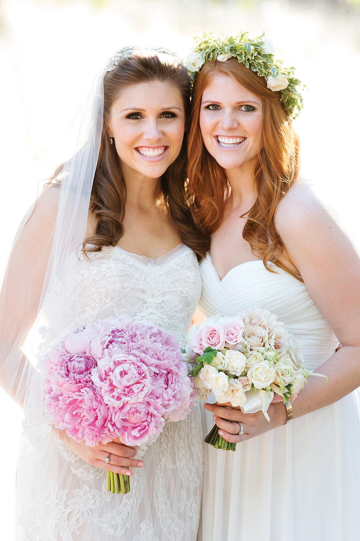 Bride in flower crown with pink wedding bouquet sister bridesmaid in flower crown