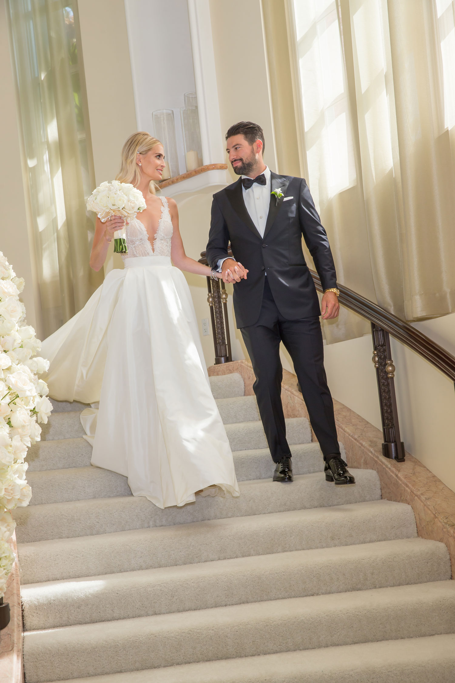 Real bride in Galia Lahav wedding dress plunging v neck ball gown long train walking down stairs