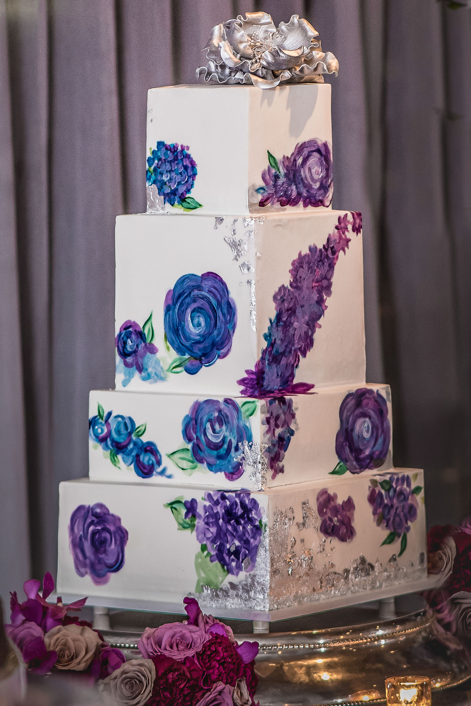 Tall white wedding cake with hand painted flowers purple blue silver designs