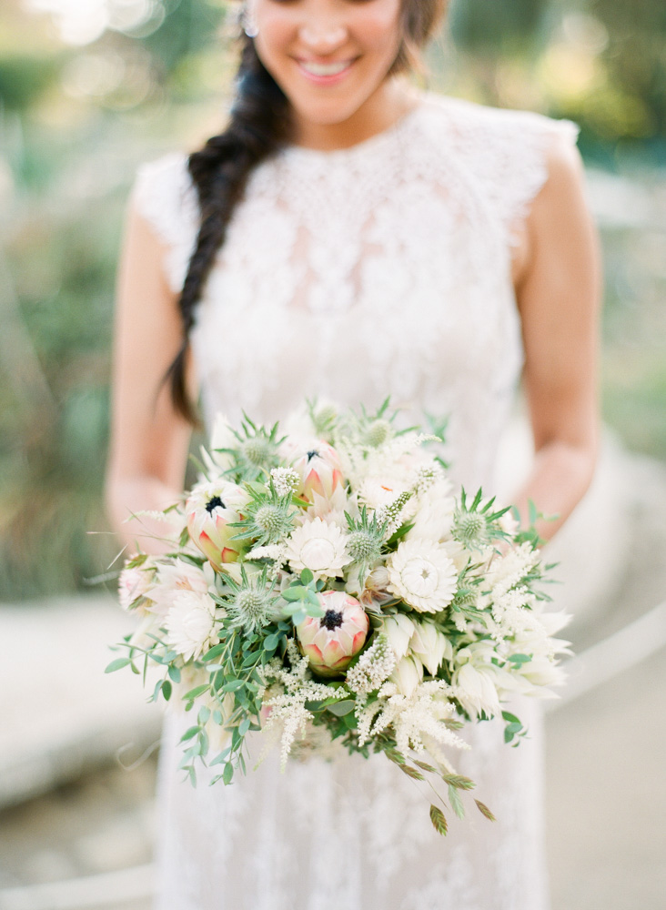 Bride in lace dress holding muted wedding bouquet with blushing bride protea flowers
