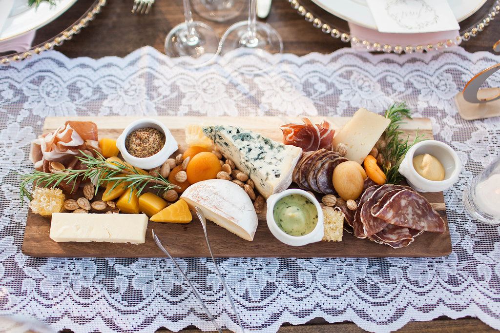 Wedding cheese and charcuterie board on lace runner