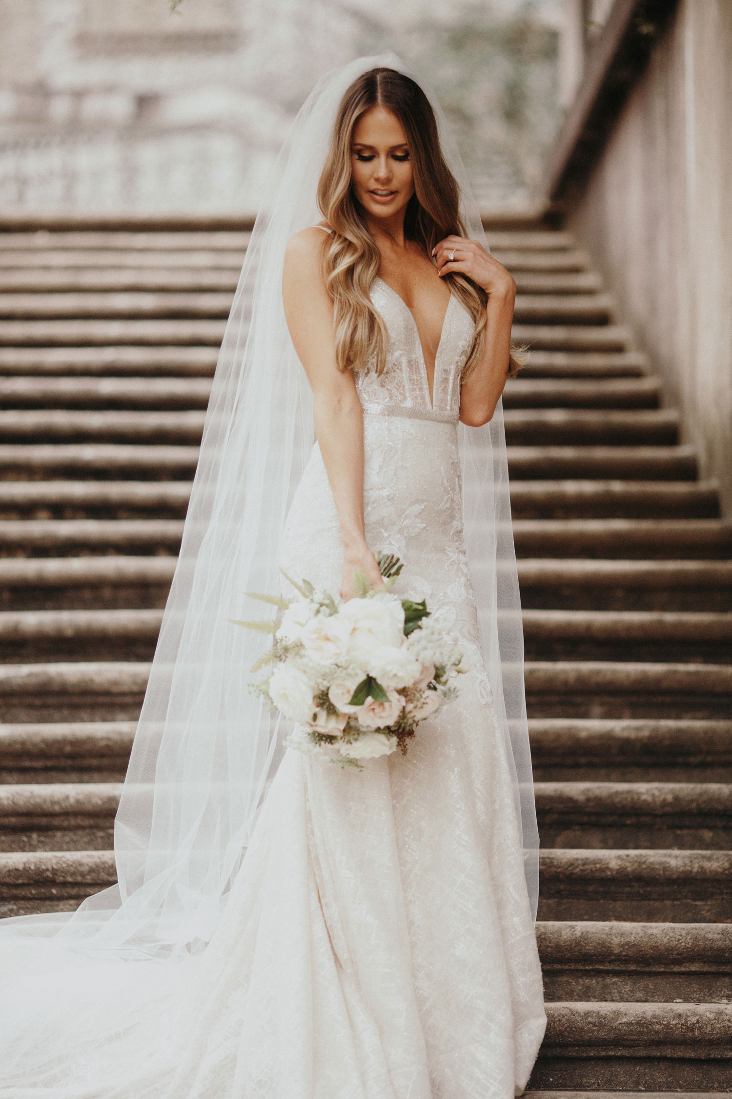 PRetty bride in low cut wedding dress cathedral veil bouquet