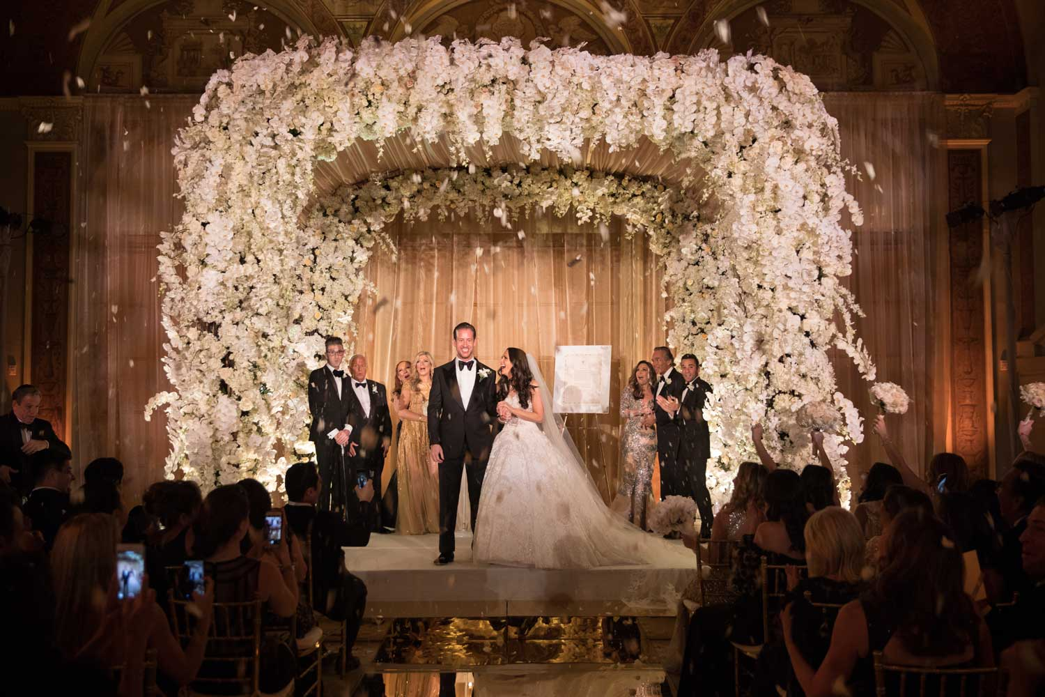 lush indoor chuppah with orchids and drapery