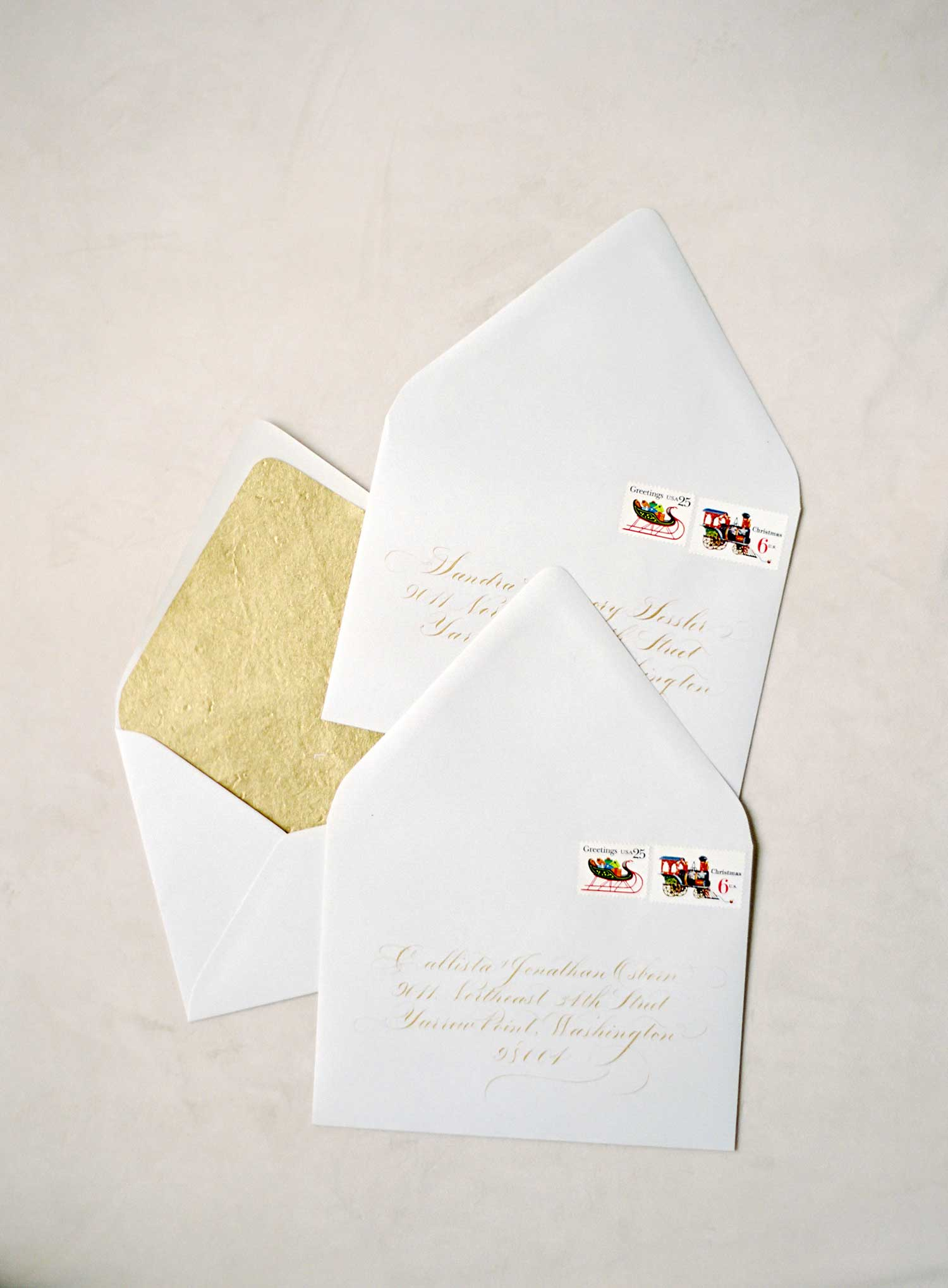 holiday entertaining party ideas white invitation with gold envelope liner christmas stamps calligraphy