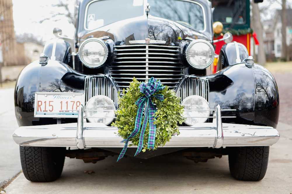 Festive wreath on wedding getaway car classic car license plate wreath and bow