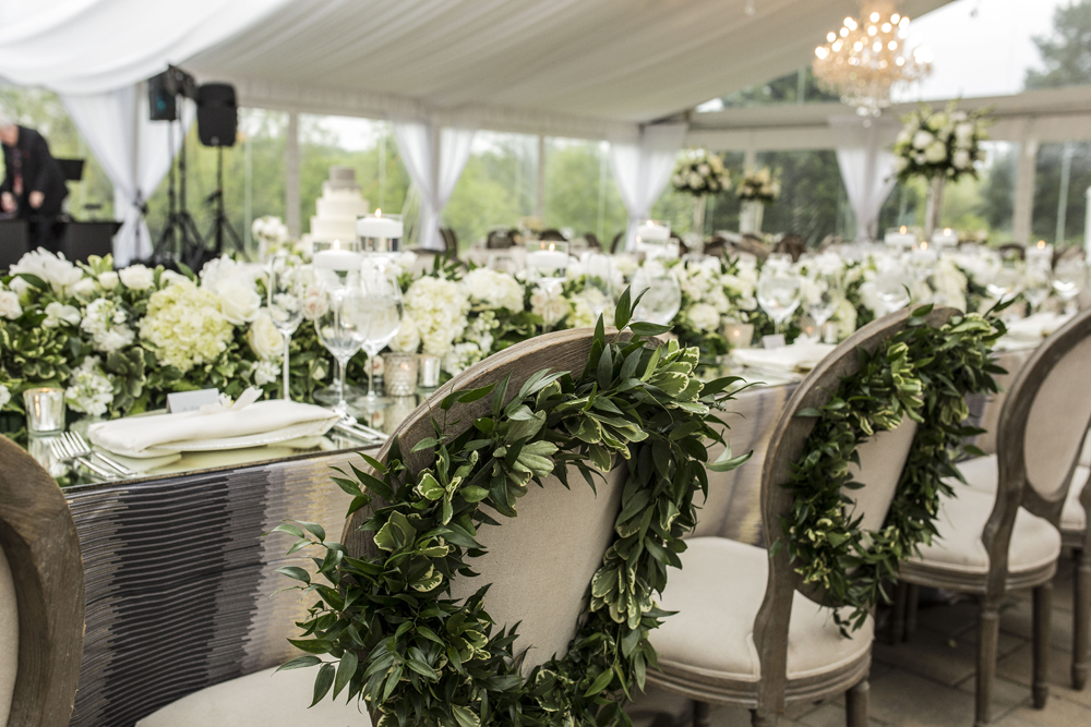 greenery wreaths on back of bride and groom chairs wedding reception neutral