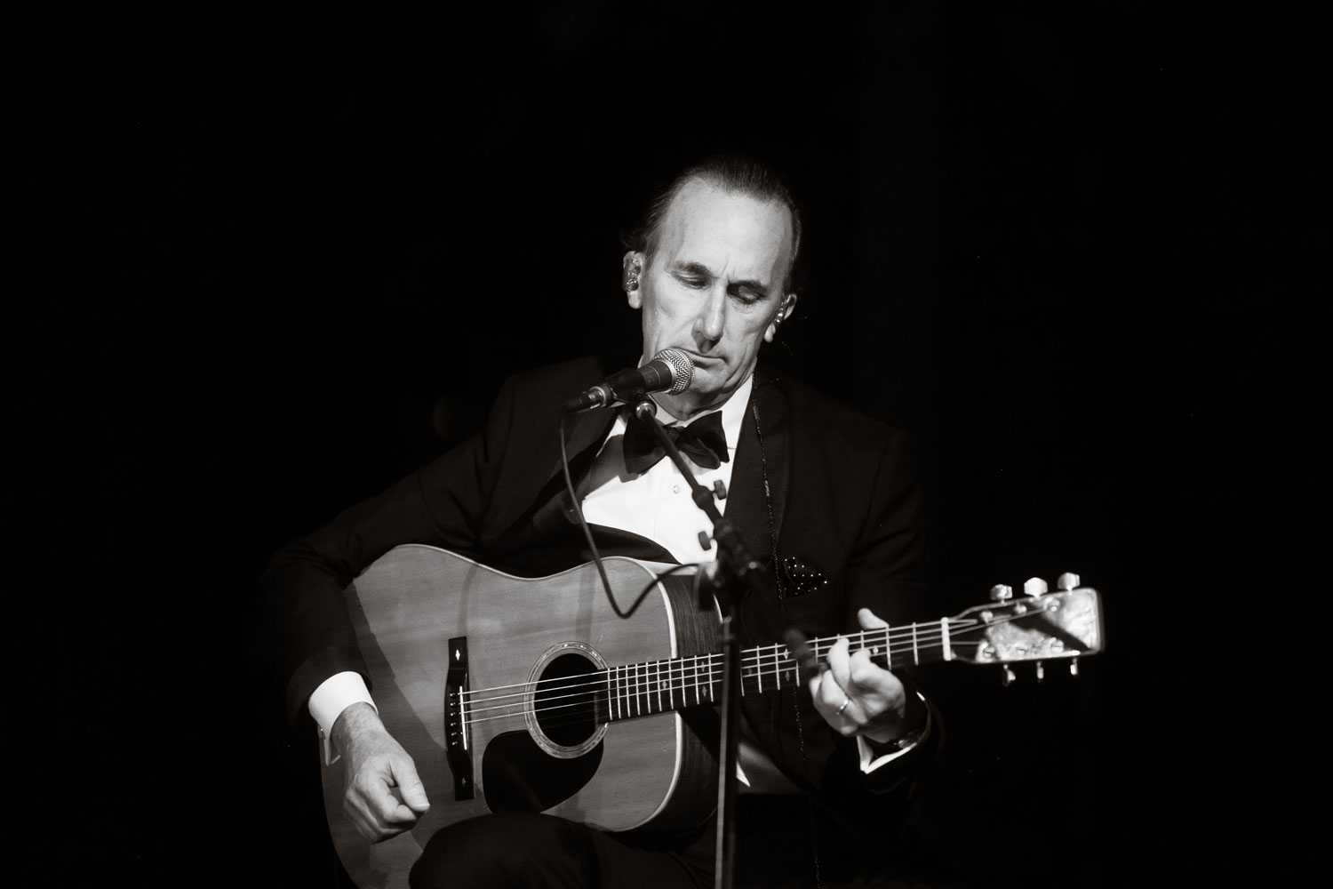black and white photo of father of bride playing guitar and performing song at wedding