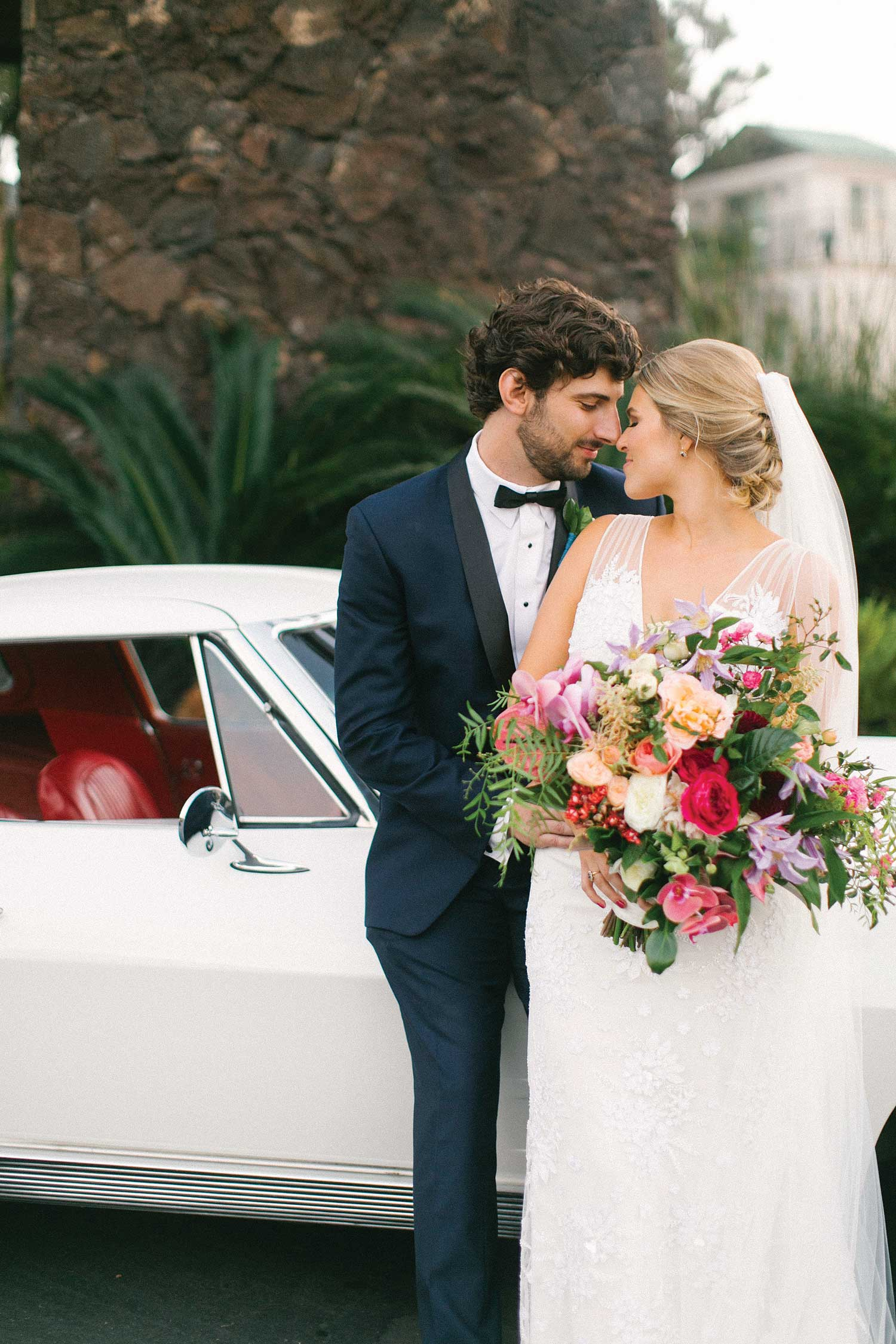 bride and groom in front of wedding car pretty colorful bouquet