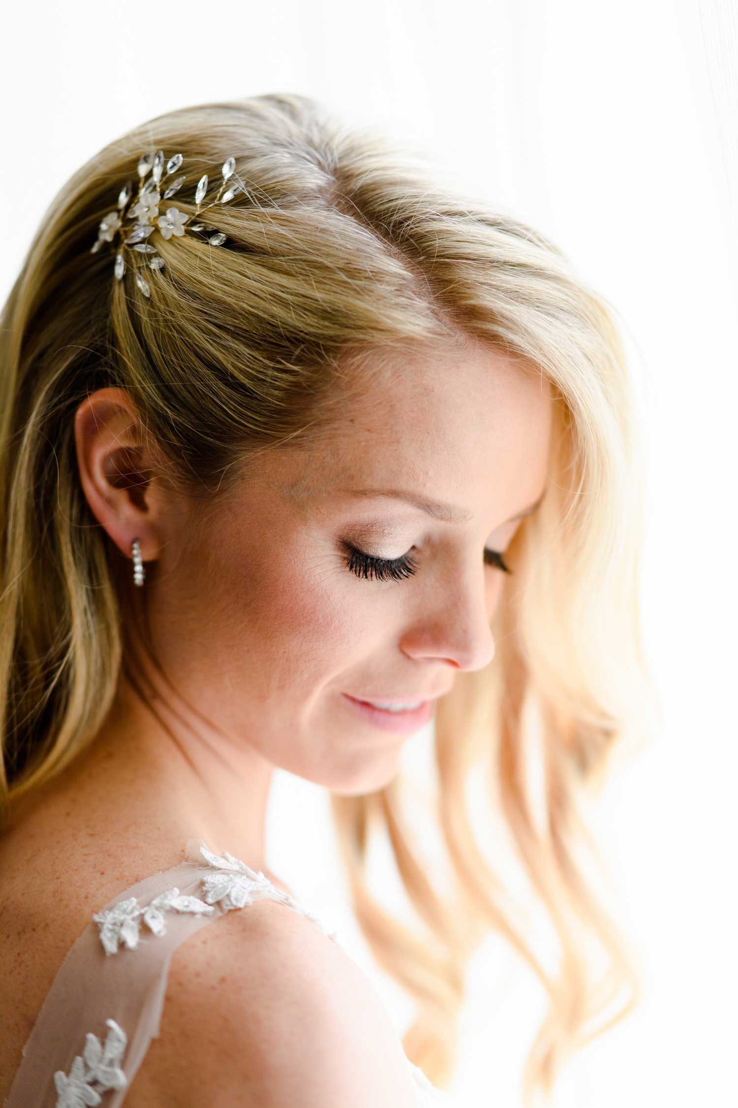pretty blonde bride with hair worn down and pulled away from face with headpiece