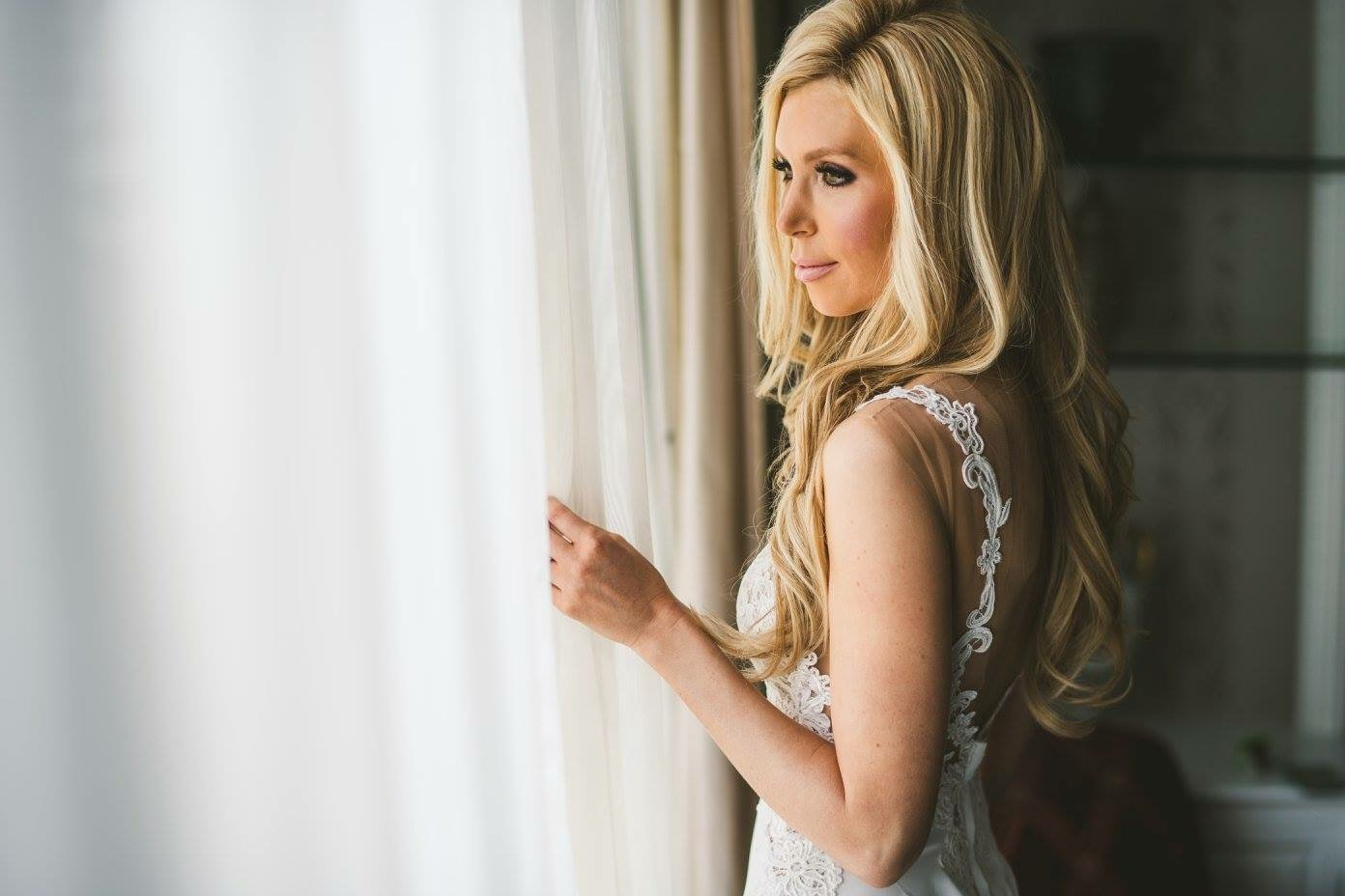 bride looking out window with long blonde hair worn down for wedding day hairstyle