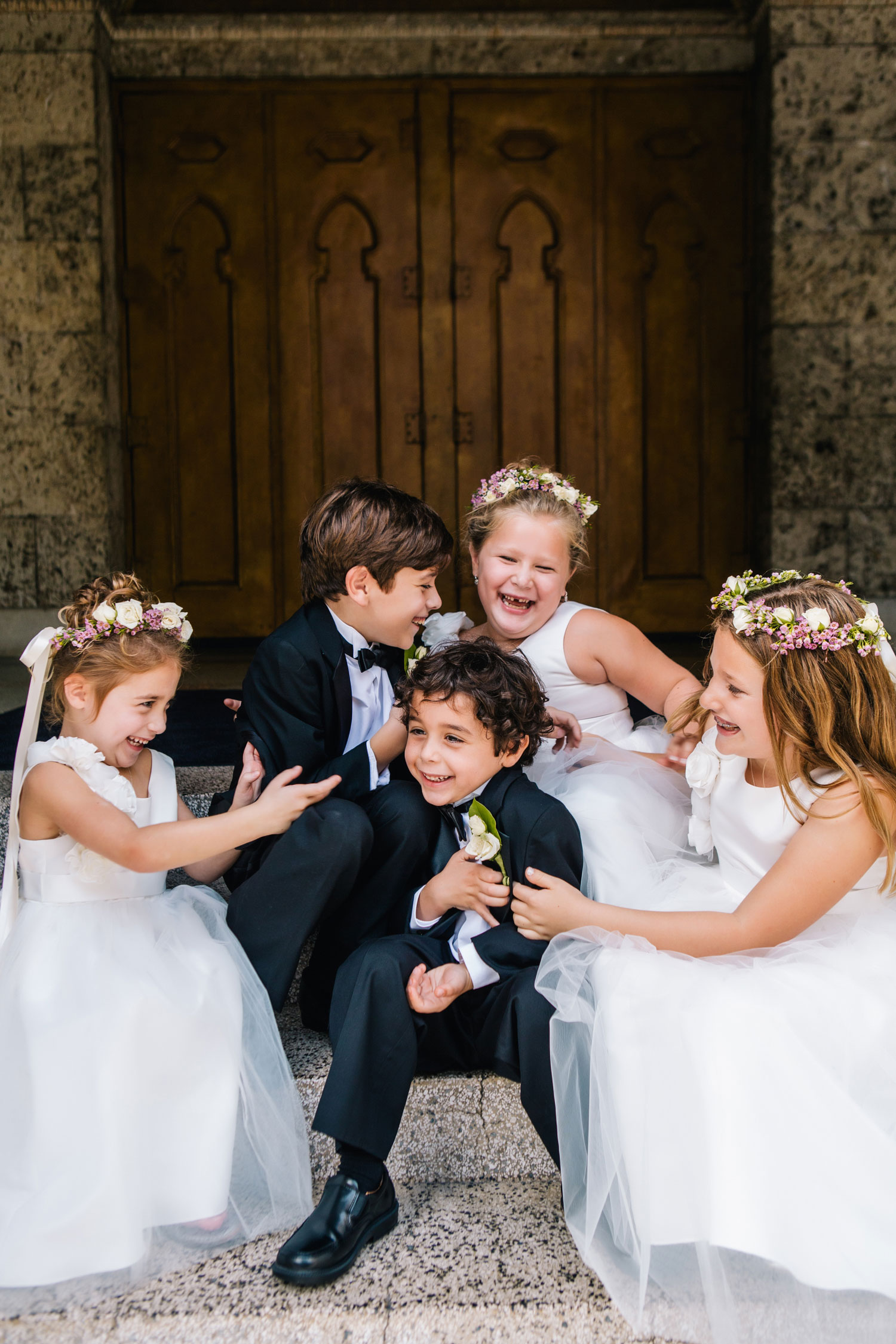 cute flower girls and ring bearers laughing and smiling on steps
