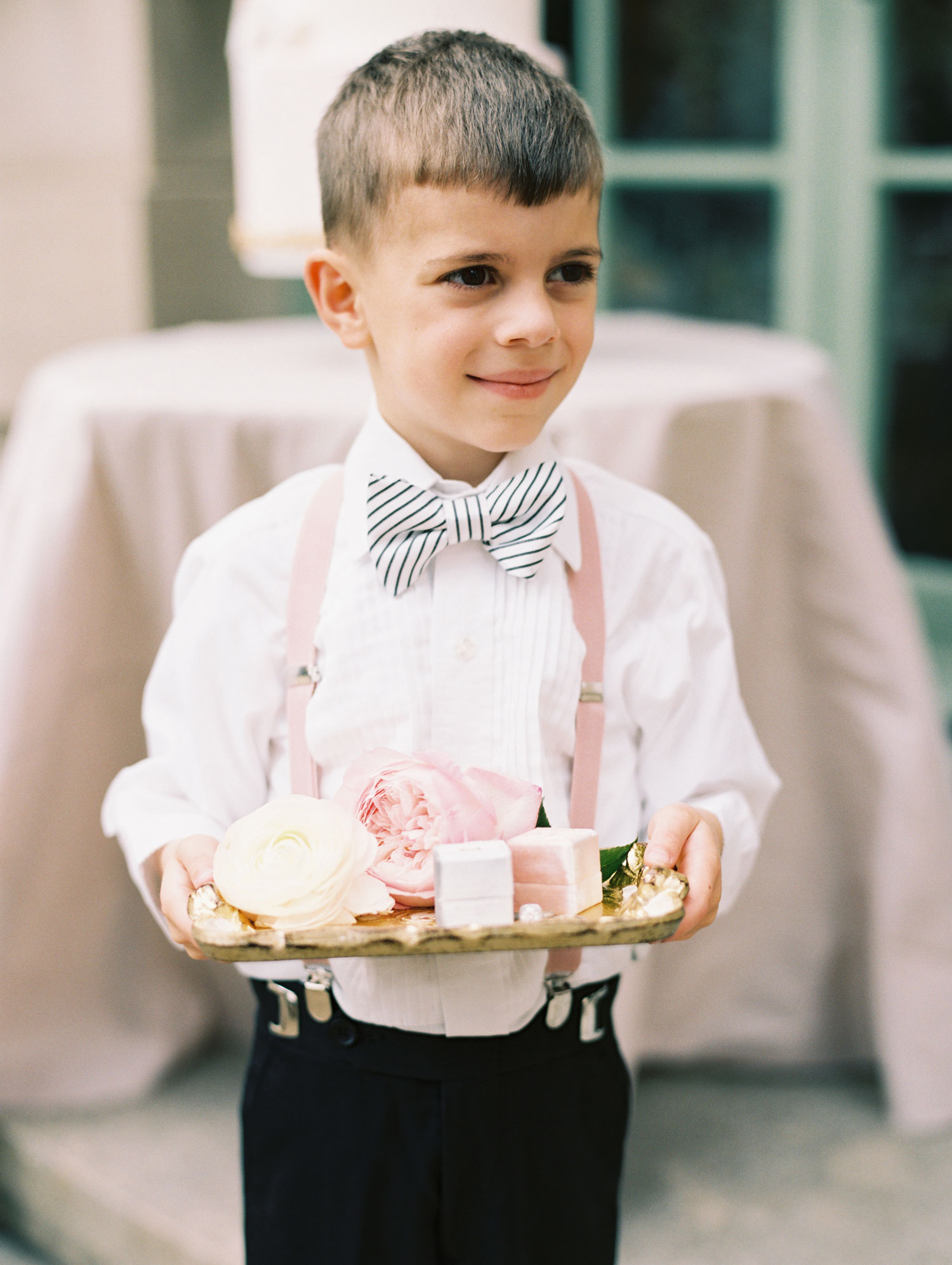 cute ring bearer holding tray with suspenders and bow tie