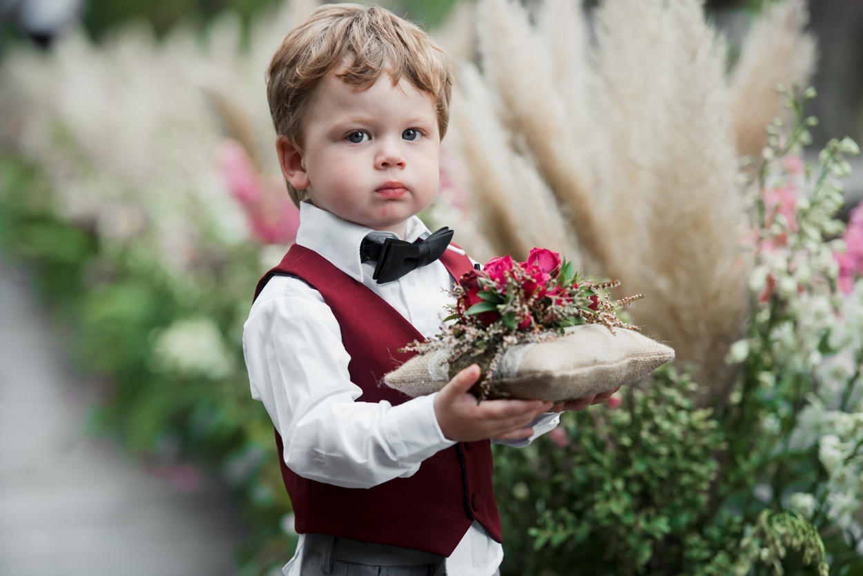 cute ring bearer in burgundy vest with ring pillow covered with flowers