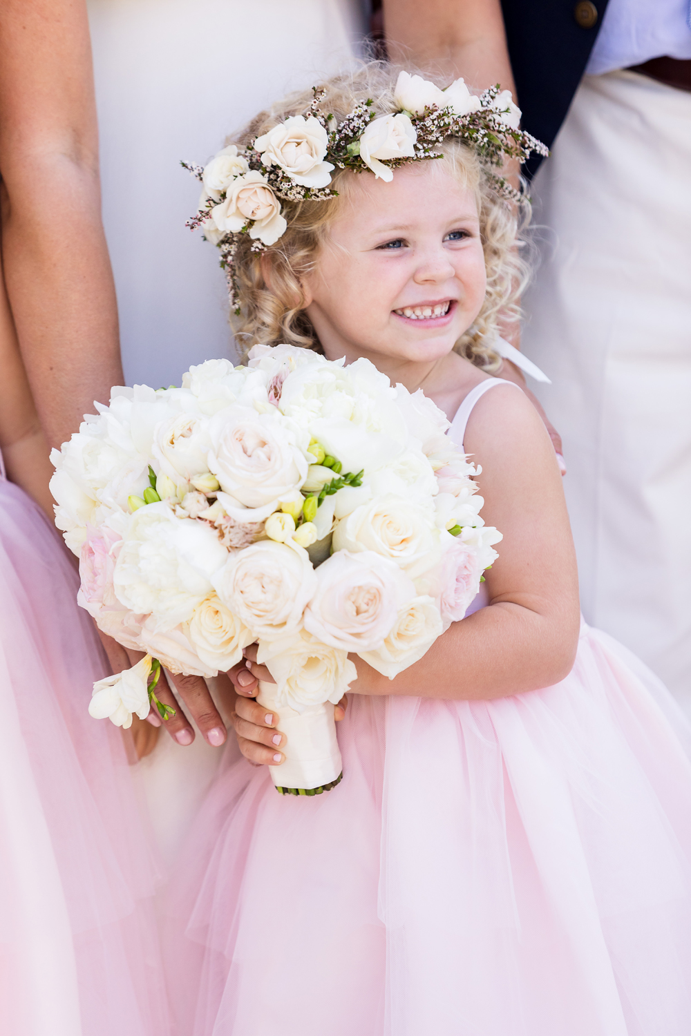 cute flower girl with curly hair with bridesmaids and bridal bouquet flower crown