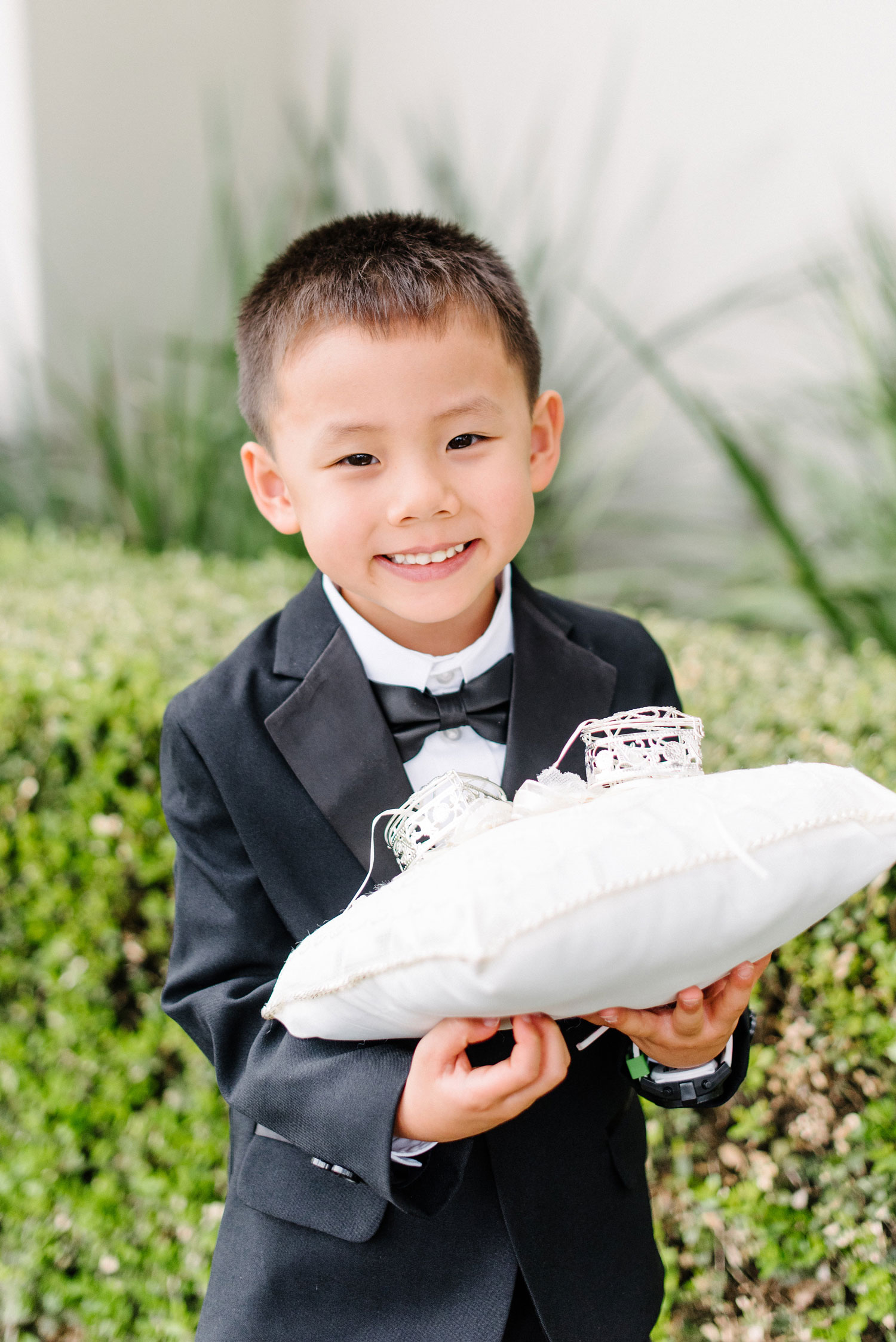 cute asian american ring bearer holding ring pillow and smiling