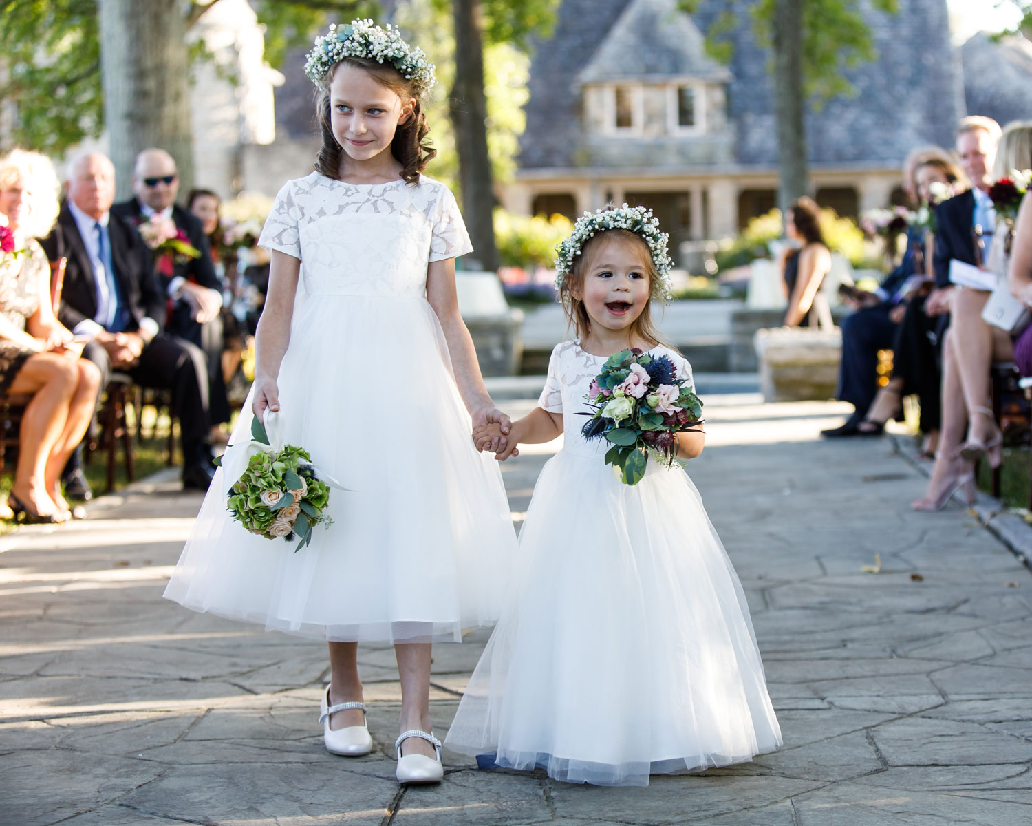 younger and older flower girl with flower crowns holding hands down aisle
