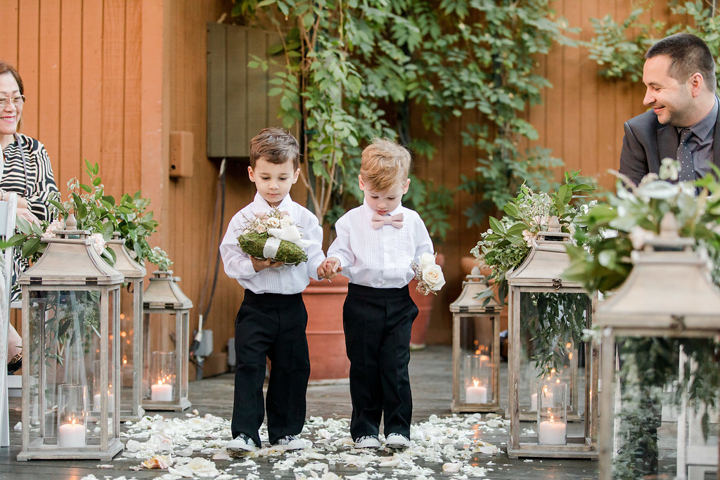 cute ring bearers in sneakers and pink bow ties walking down ceremony aisle