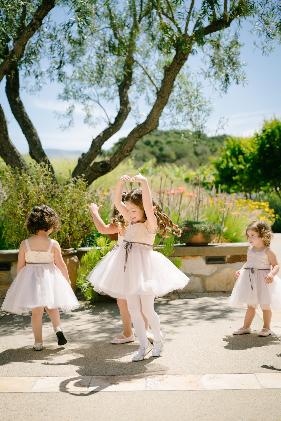 cute flower girls twirling and dancing at outdoor wedding