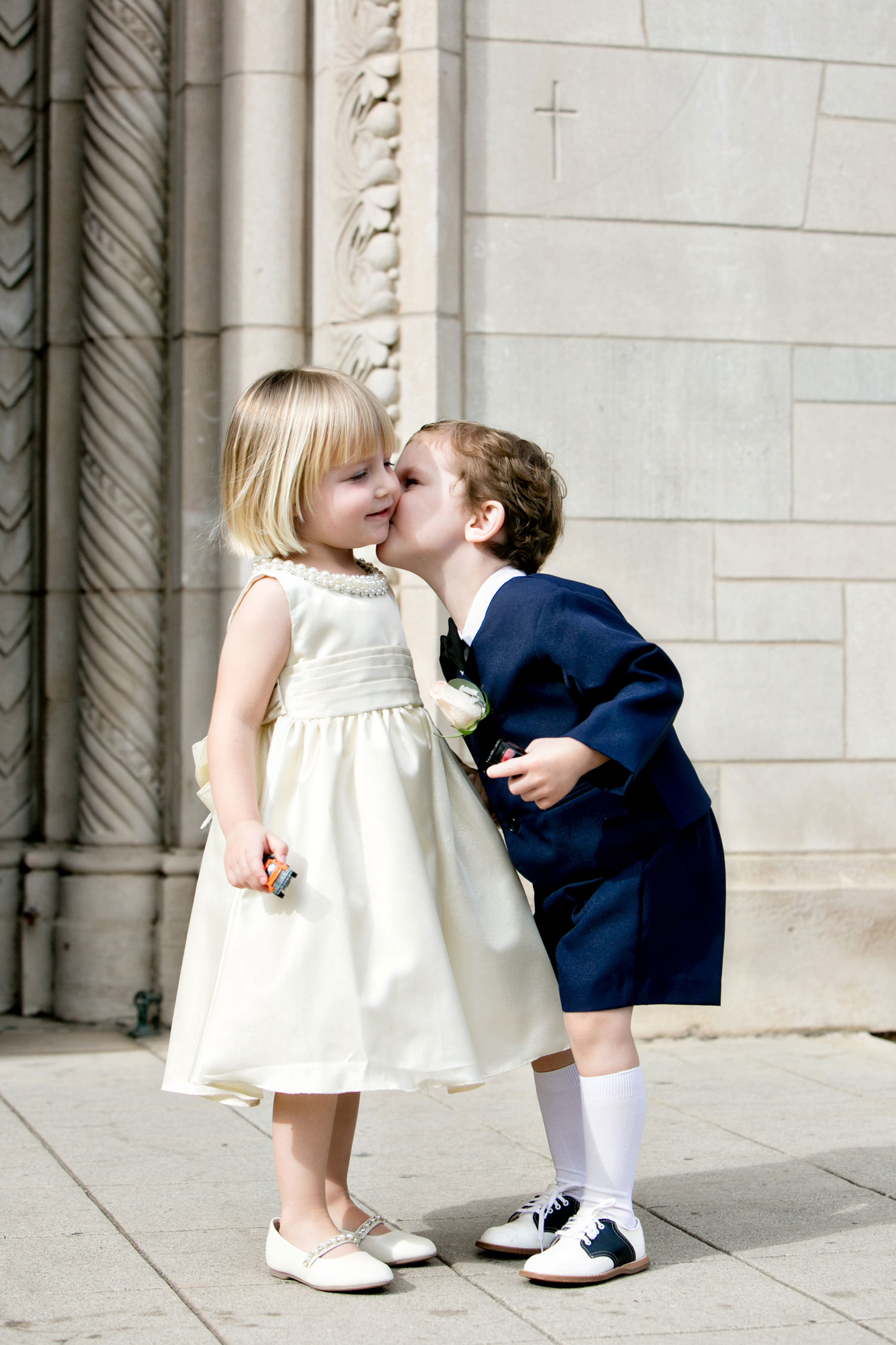 cute flower girl and ring bearer giving kiss at wedding old fashioned outfits short suit