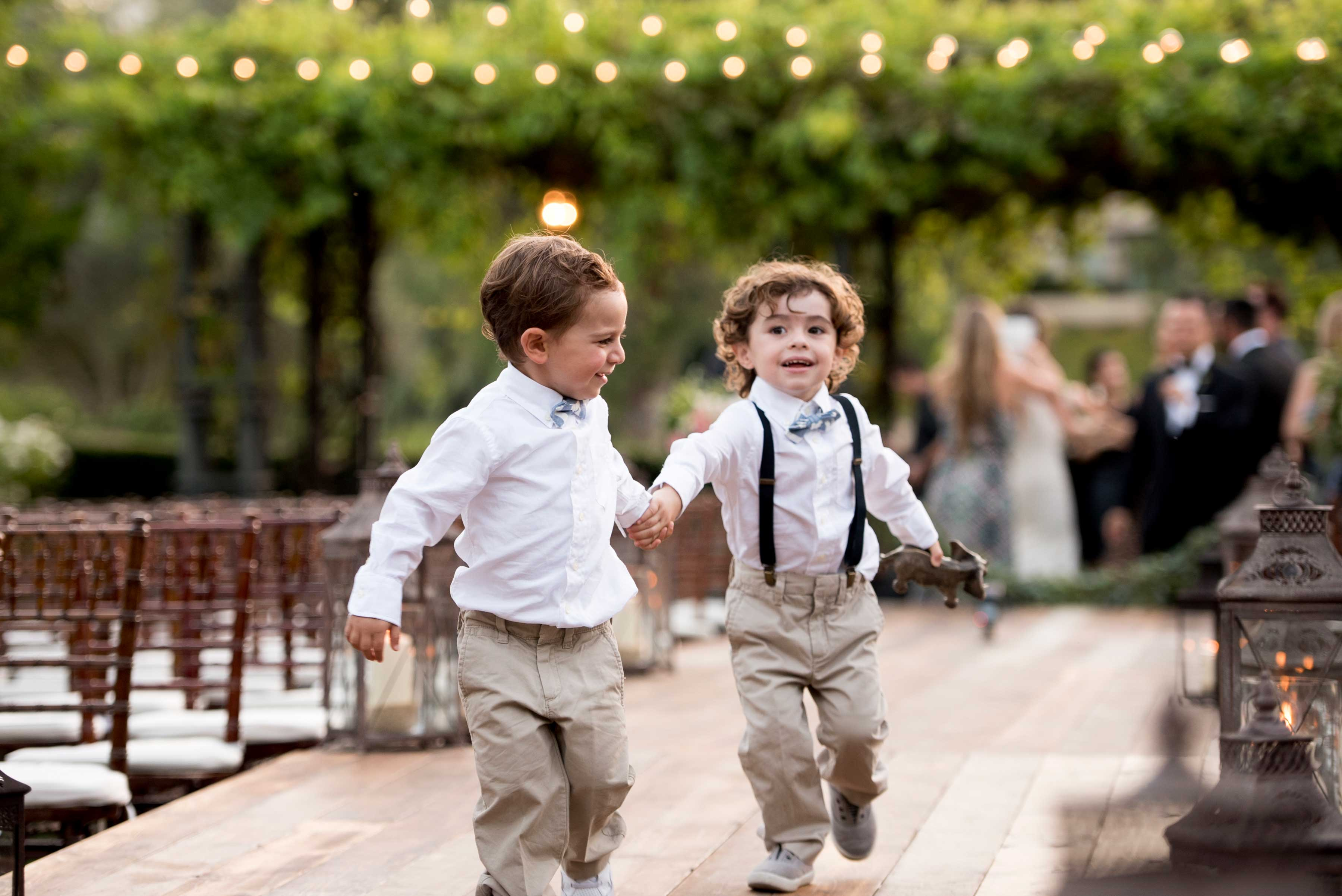 ring bearers holding hands in bow tie suspenders running down wood aisle