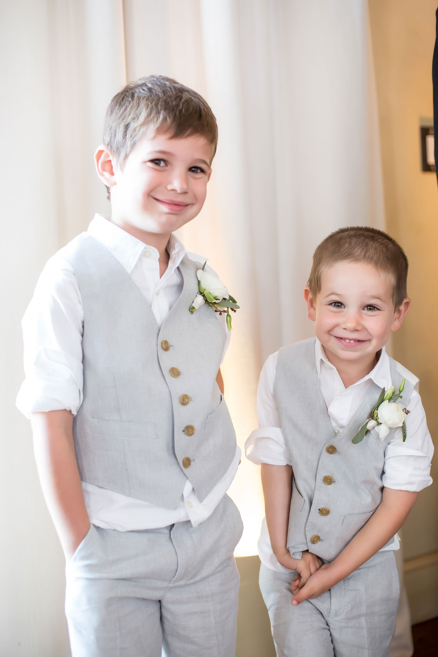 Cute ring bearers at wedding in grey slacks and grey vests smiling hands in pockets