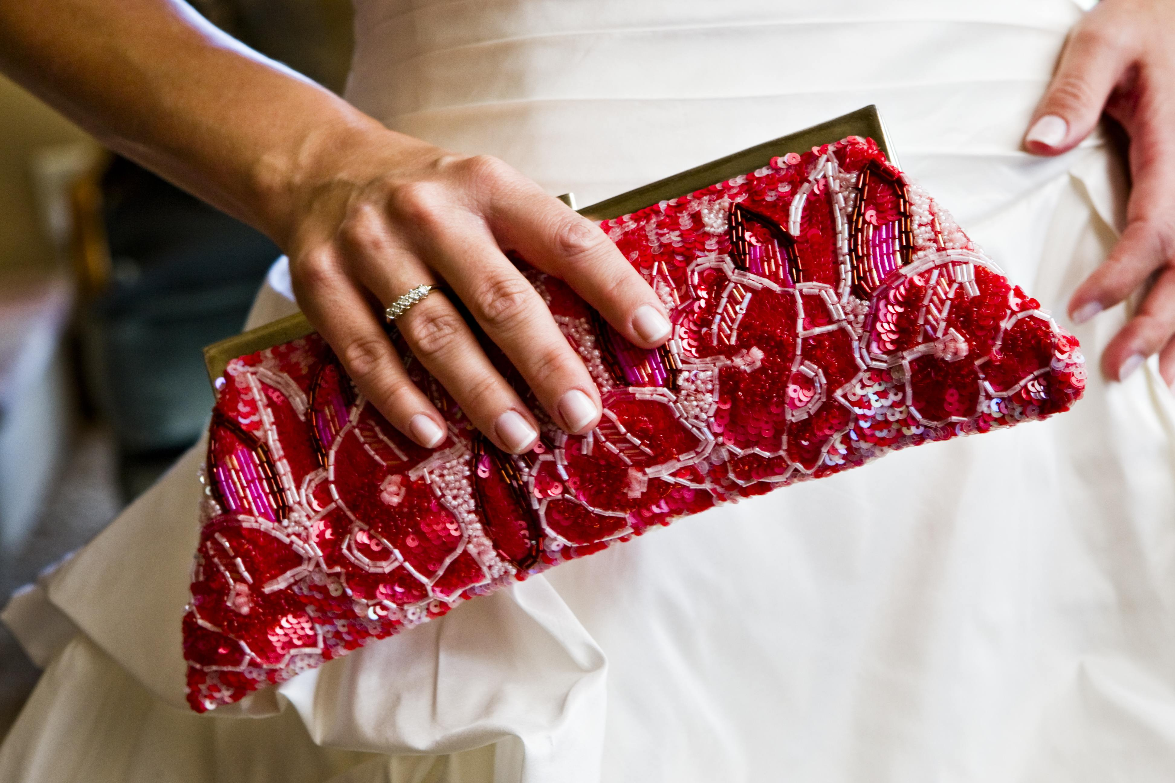 bride with wedding ring holding beaded clutch bridal wedding purse pink red