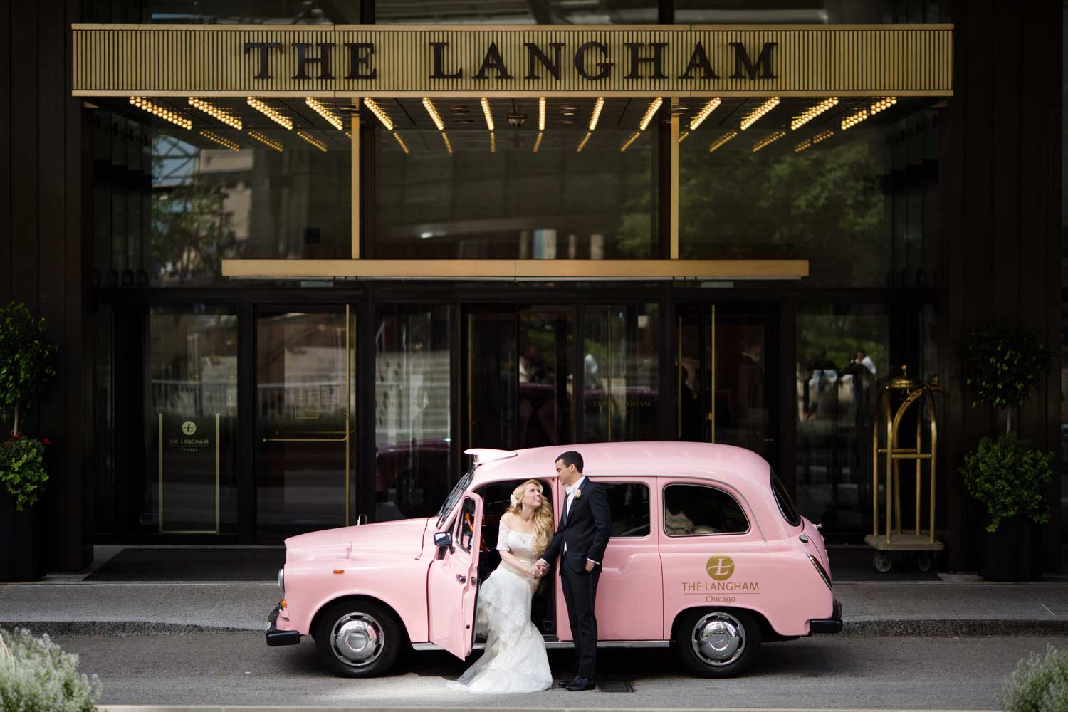 Bride and groom getting into pink london taxi style cab langham hotel