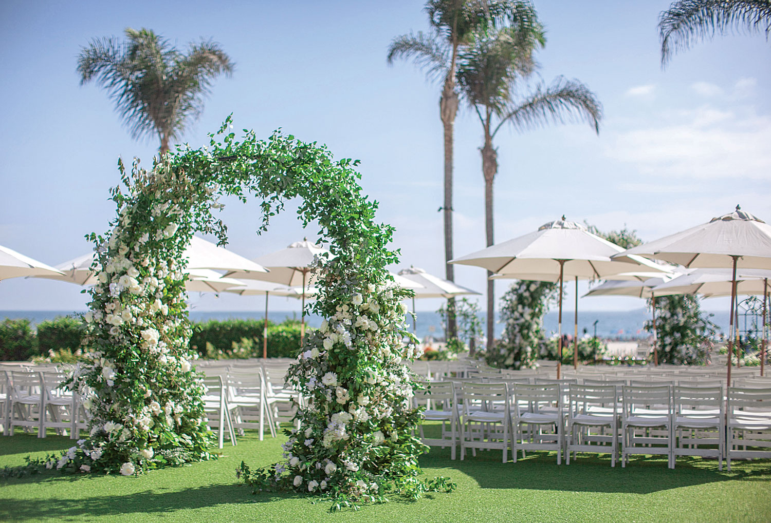 Inside Weddings magazine Spring 2019 issue outdoor oceanfront wedding ceremony greenery arch